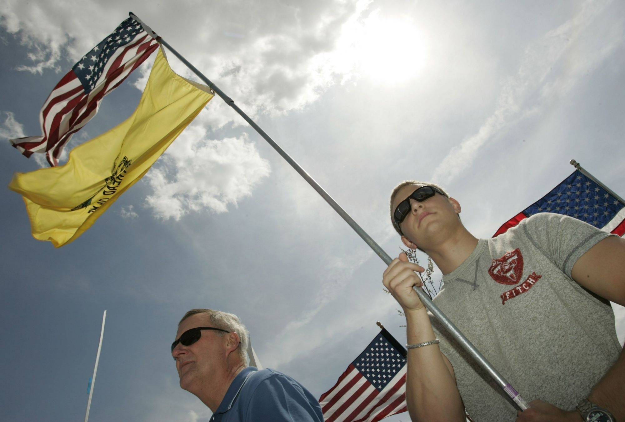 Alex Dubinski of Algonquin hoists flags high on Thursday during a tea party rally at Cornish Park in Algonquin.