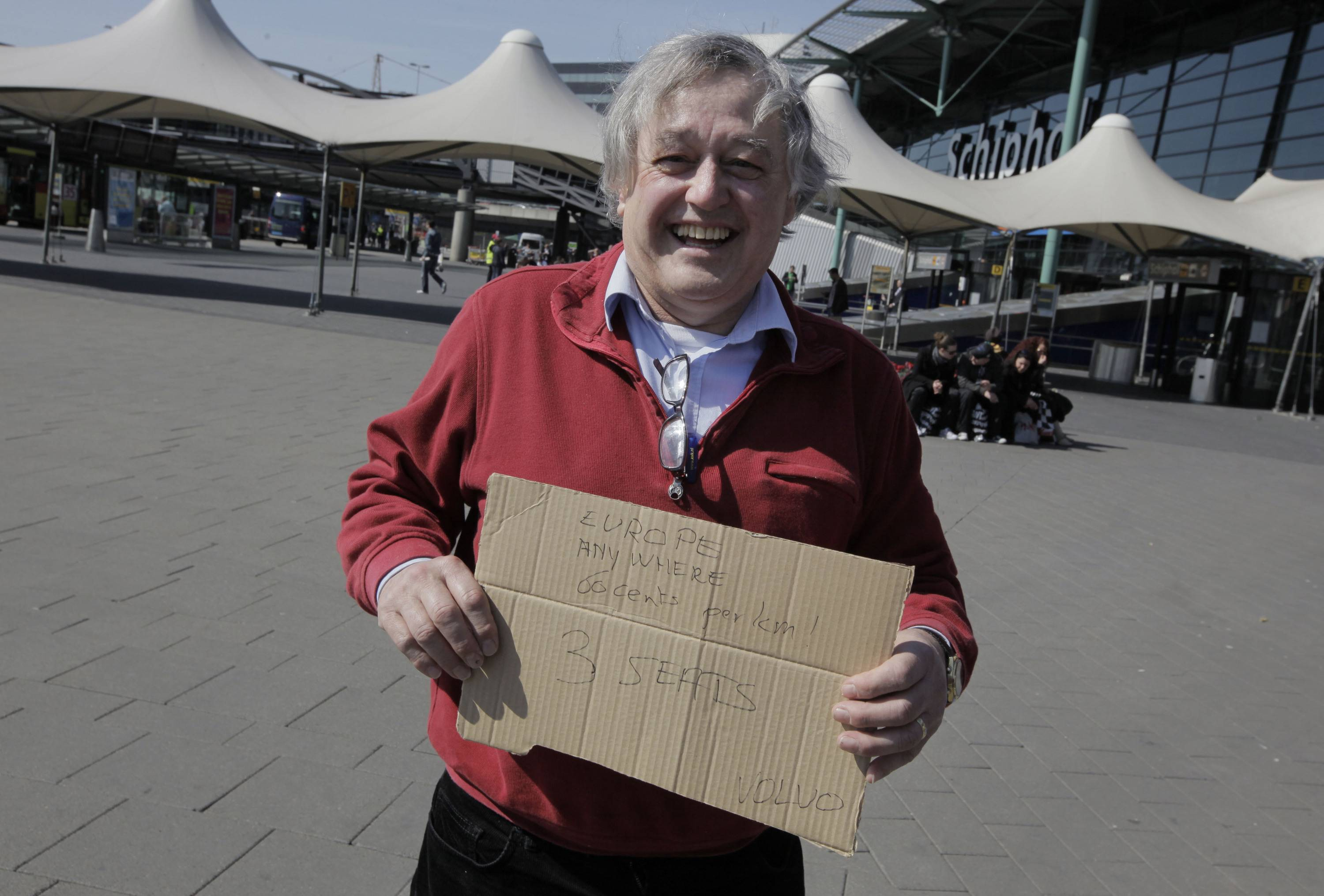 A man holds a sign offering to drive stranded travelers to any location in Europe for 0.60 euros per kilometer at Schiphol Airport, Amsterdam.