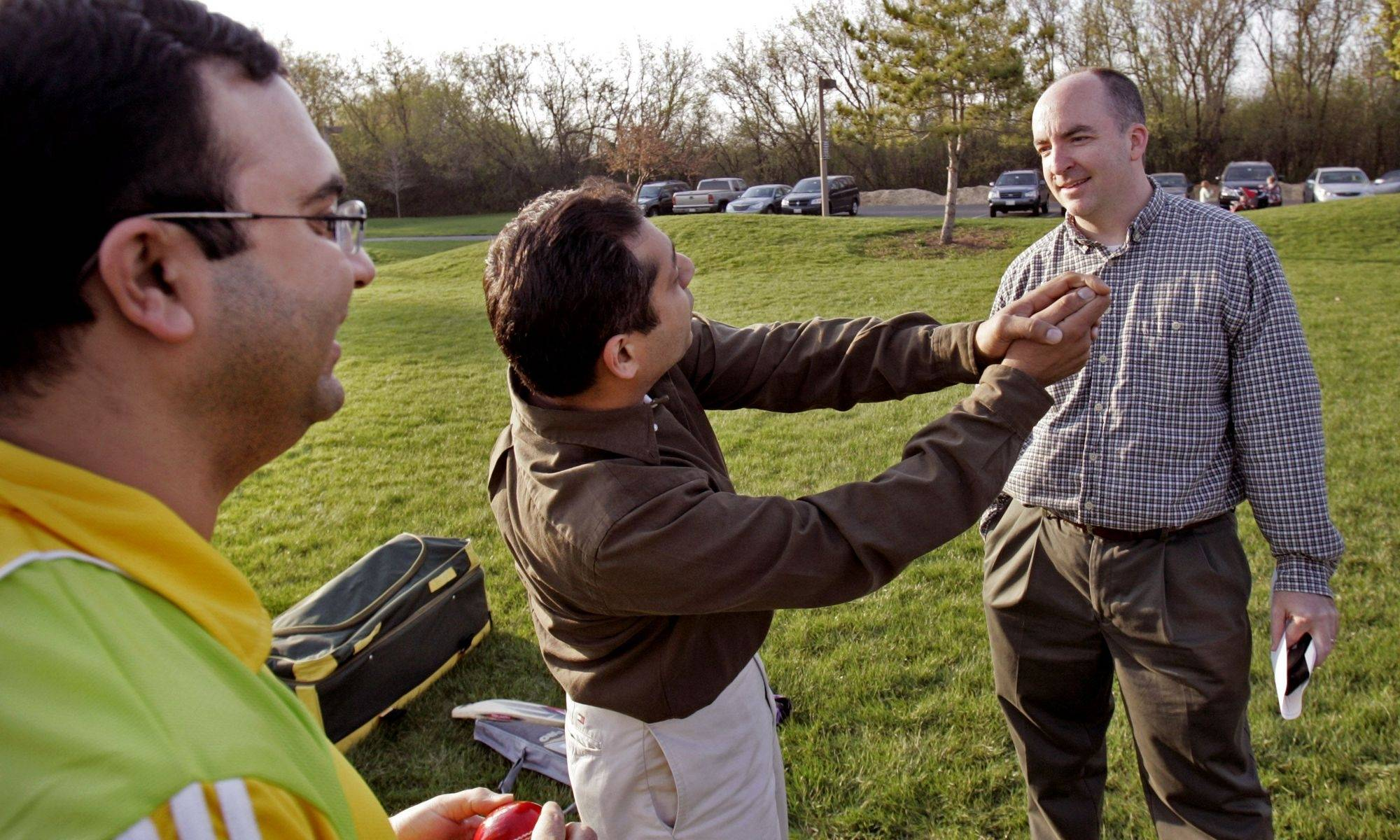 Mukarram Raheel of Mundelein, left, and Bobby Tuli of Buffalo Grove explain the rules of cricket to Tom Ritter, superintendent of recreation for the Vernon Hills Park District.