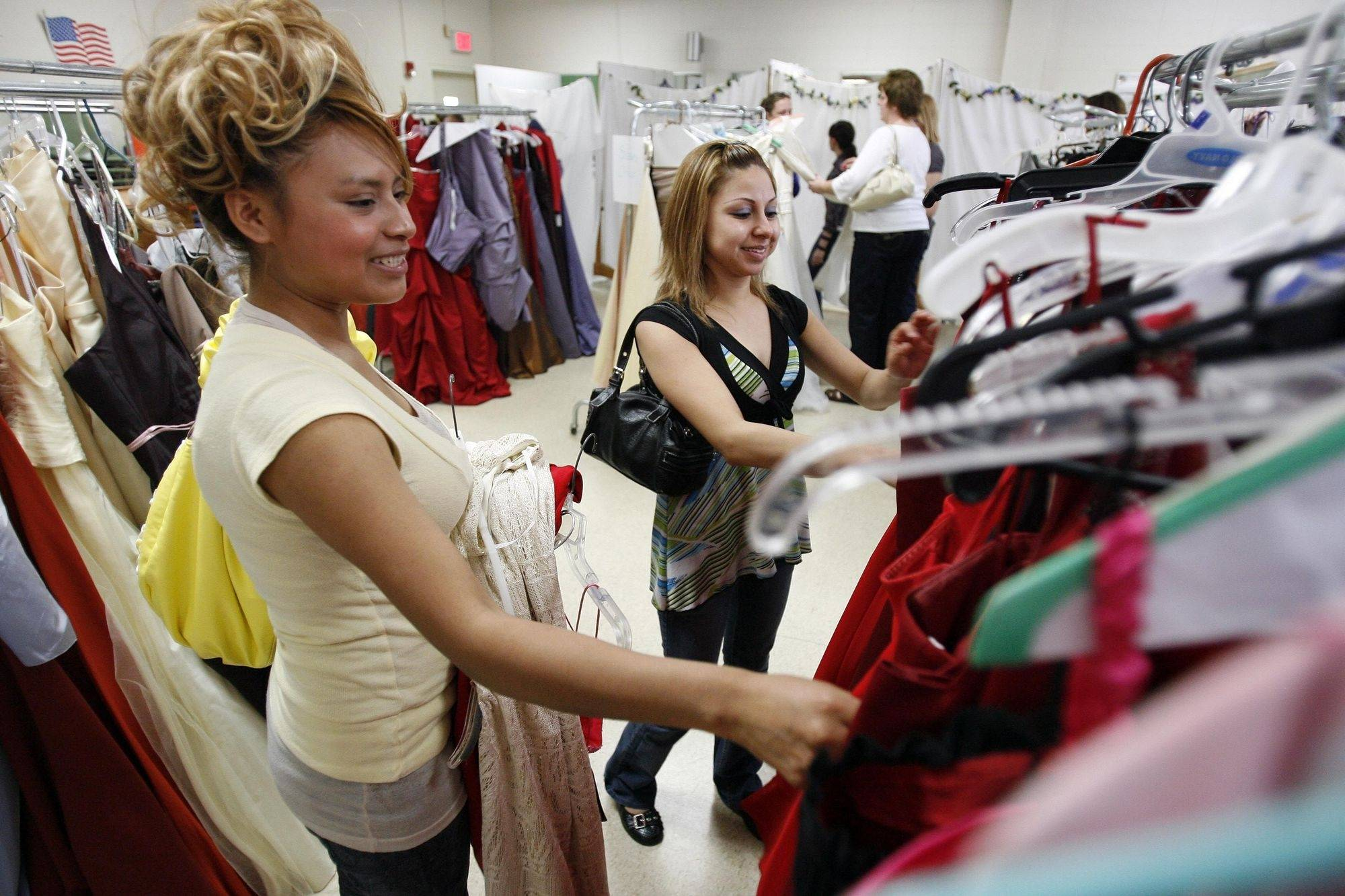 Eighteen-year-old Maribel Teapila, of Streamwood, left, gets some help from her friend Lucia Figeroa, 24, of Glendale Heights as she looks for a prom dress during the sale Saturday at the YWCA in Elgin.