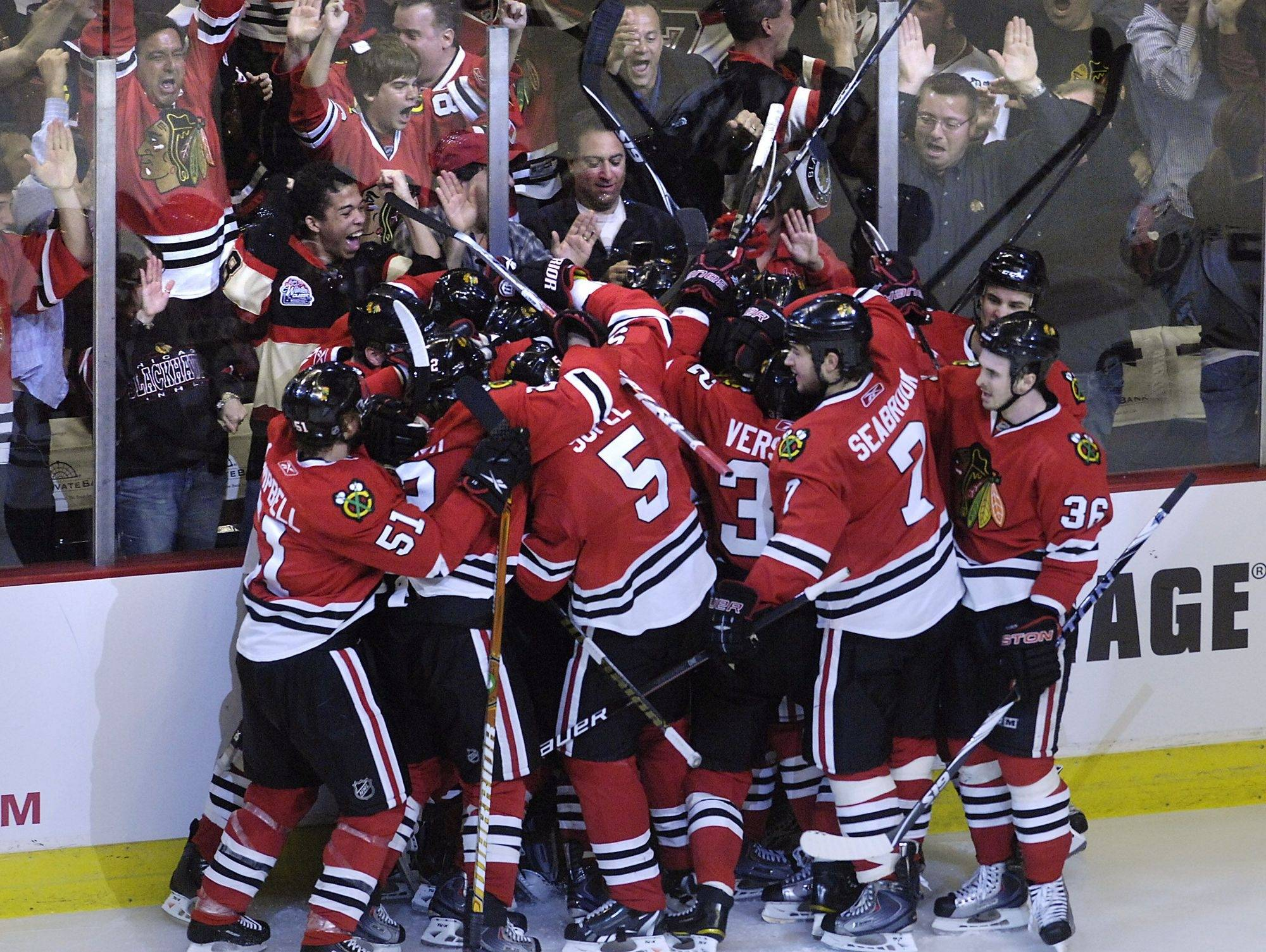 Chicago's Marian Hossa is overcome by his teammates after he scored the game-winning overtime goal against the Nashville Predators Saturday at the United Center in Game 5 of the first-round Stanley Cup playoff series.