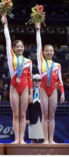Chinese gymnasts Yang Yun, left, and Dong Fangxiao wave flowers after receiving the bronze medal in the women's gymnastic team finals at the 2000 Summer Olympic Games in Sydney. China was stripped of a bronze medal Wednesday for fielding an underage female gymnast.