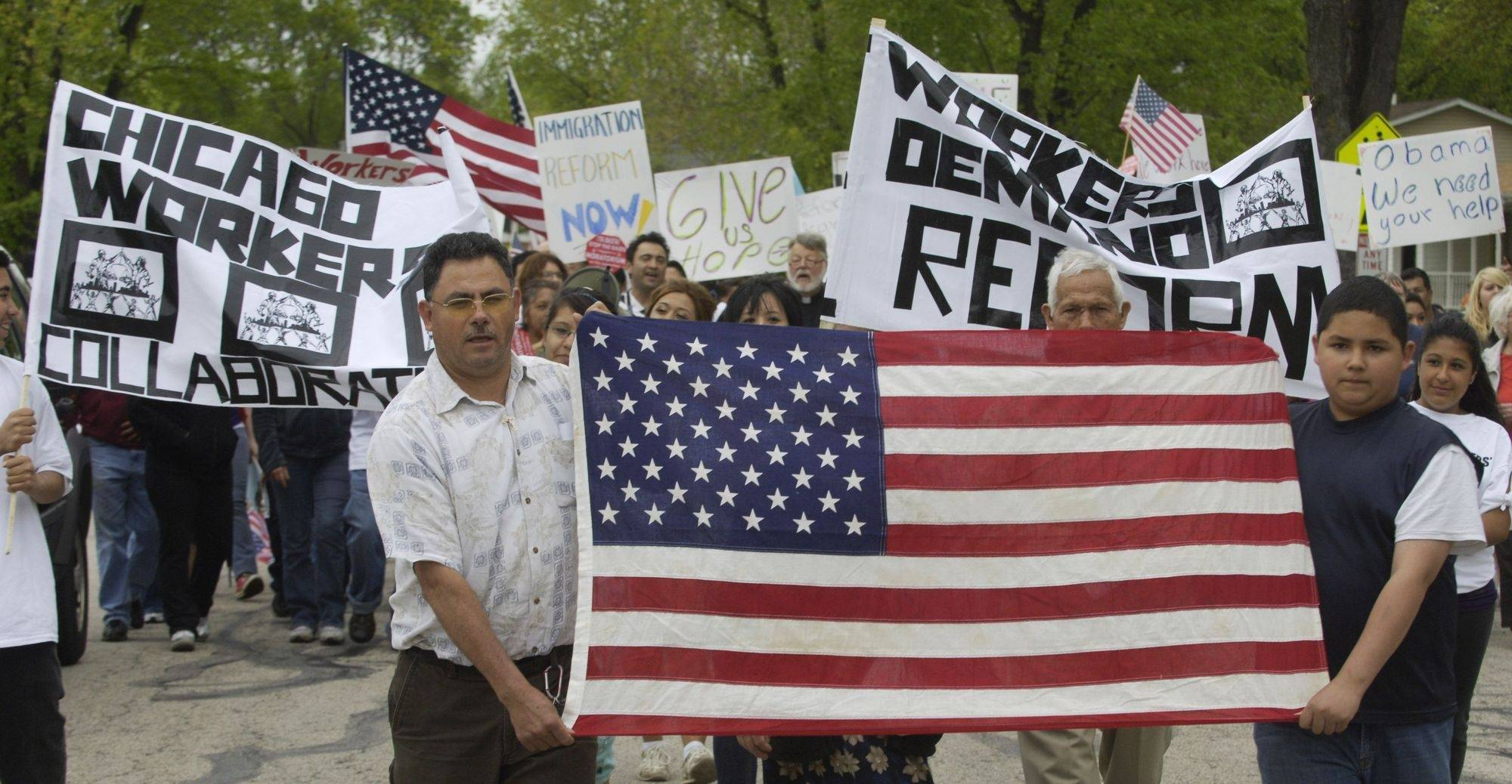 Efren Espino, left, of Round Lake, and his son, Efren Jr., carry the American flag at the front of a pro-immigration reform march along Anderson Drive in Palatine Saturday.
