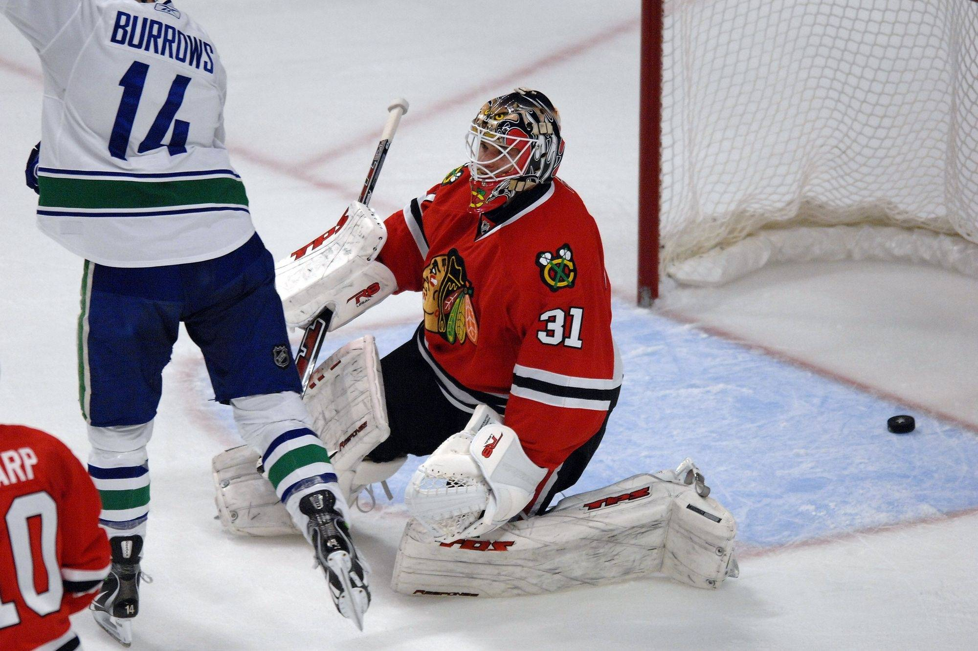 Hawks goalie Antti Niemi watches as Vancouver starts to celebrate a first period with this goal.