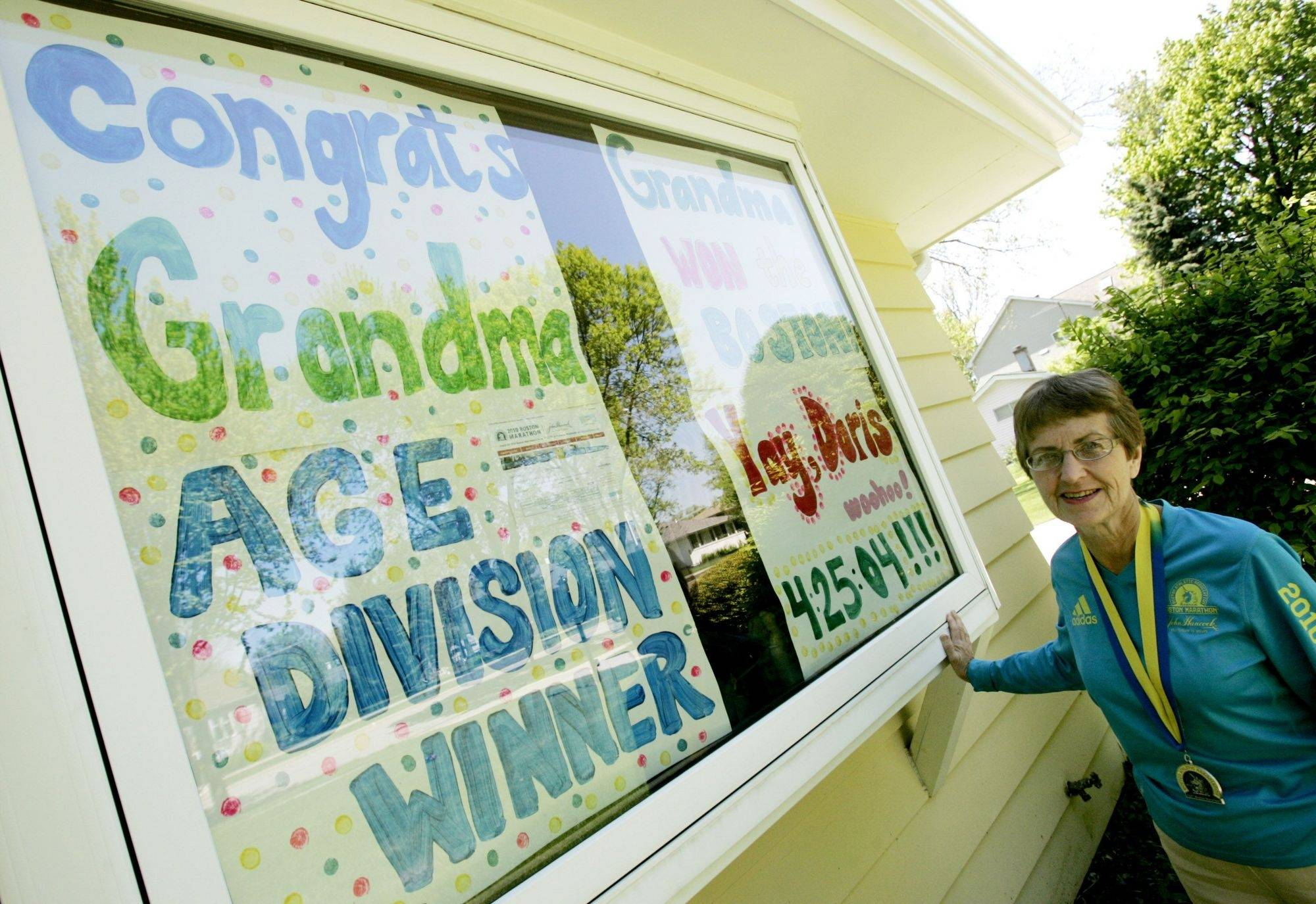 Doris Schertz, 71, came home from the Boston Marathon with a first-place medal in her age category. Her proud grandchildren filled the front window of her Lombard home with handmade congratulations.