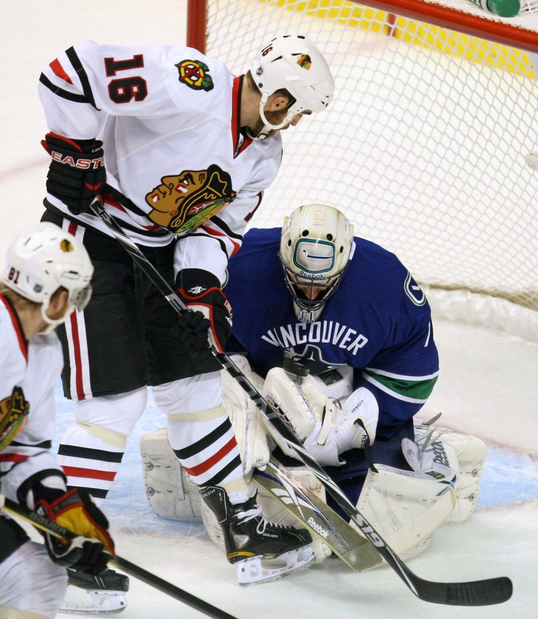 Vancouver Canucks goaltender Roberto Luongo, right, stops Chicago Blackhawks' Andrew Ladd during the first period .