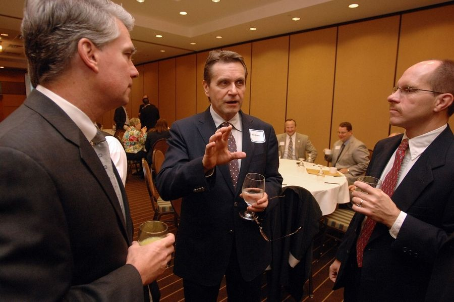 Bob Mariano, chairman and chief executive officer of Roundy's Supermarkets Inc., center, talks with Michael Mallon, left, and Dan Farrell at a Wednesday breakfast sponsored by the Arlington Economic Alliance.