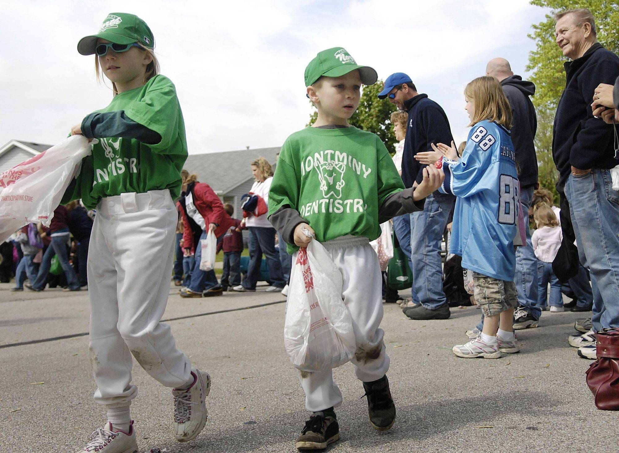 Shannon Lopresti, 9, and brother Tony, 7, of the Montminy Dentistry baseball team hand out candy individually to people along the parade route for the North Aurora Mother's Club and North Aurora Baseball Association last year.