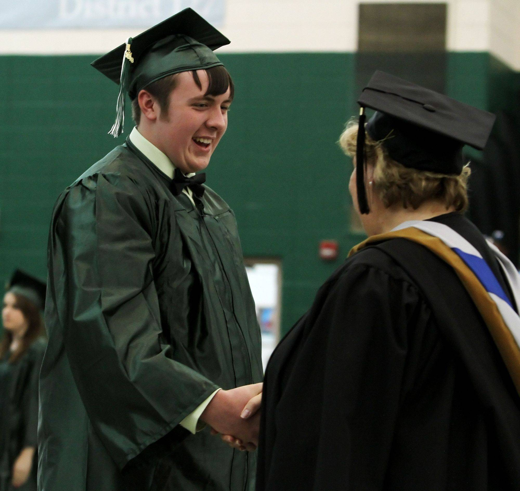 Joseph Domka shakes Principal Sydney Klocke's hand after receiving his diploma during the graduation ceremony Sunday at Grayslake Central High School.