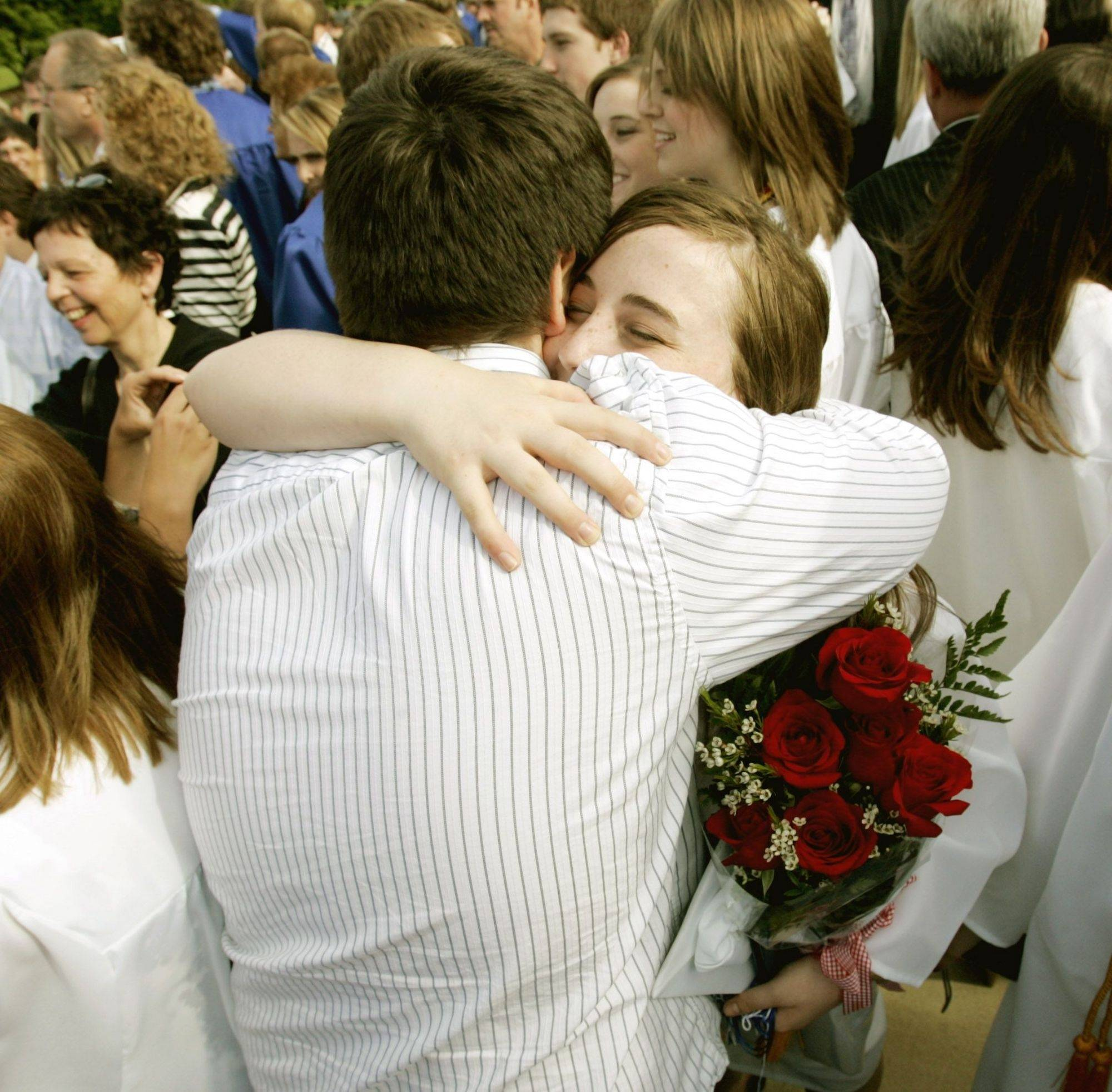 Mike Workman,left, of Bloomingdale gives Brittany Riesenbeck,right, a hug after theSt. Francis High School graduation ceremony Sunday at St. John Neumann Catholic Church in St. Charles.