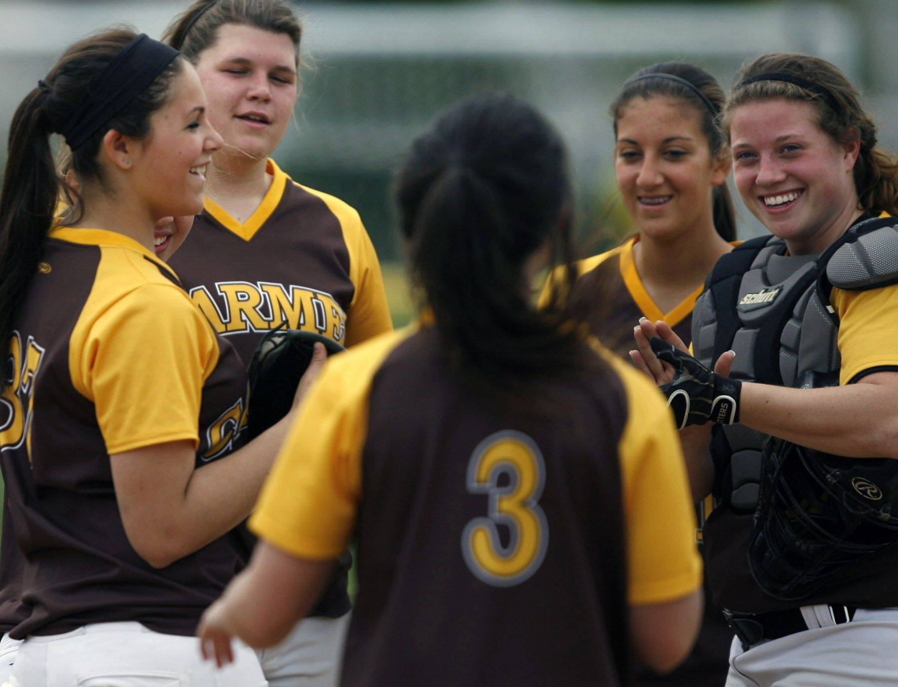 Carmel pitcher Rachel Tack (3) is greeted by teammates, from left, Danielle Pullano, Sally Snarski, Eden Warnke and Meg Grady, after returning to the field after a hand injury.