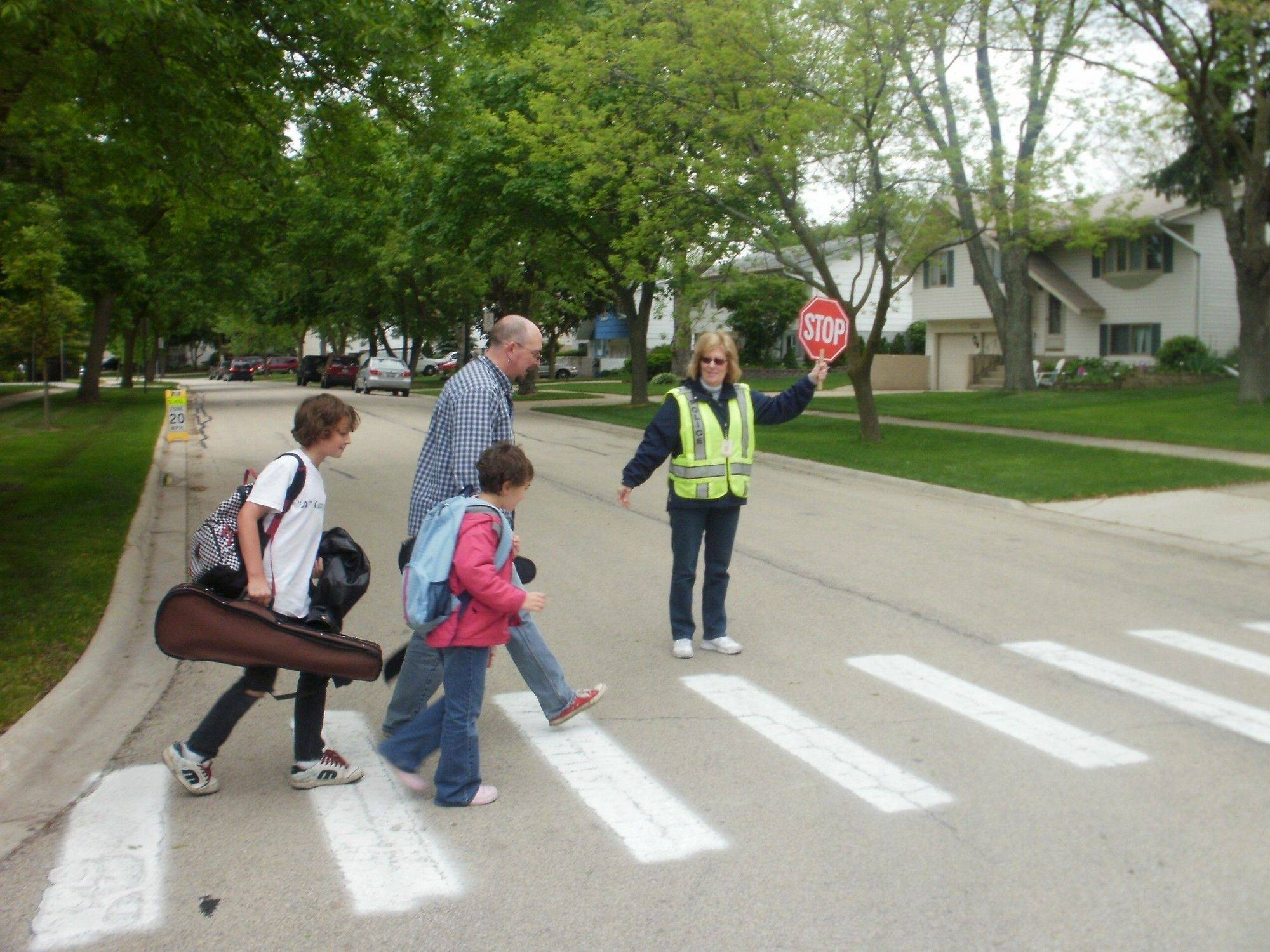 Crossing guard Jan Stiefvater lends assistance and a smile to Hayden and Savannah Sherrell, walking home from Dooley Elementary School in Schaumburg with their dad, James Sherrell.