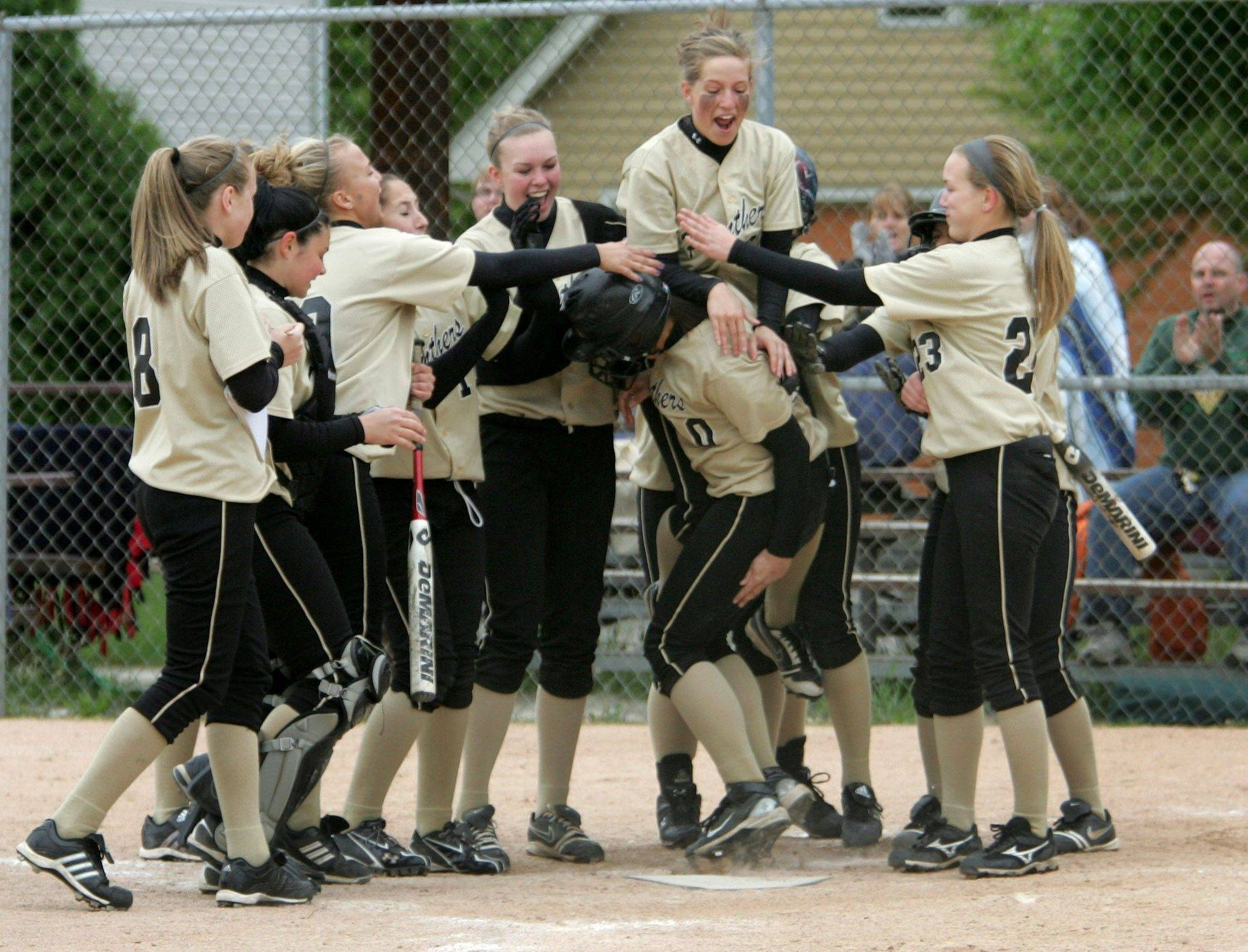 Glenbard North teammates greet Jenny Nelson, center, after she hit a 2-run homer in the fifth inning against West Chicago during softball on Monday.