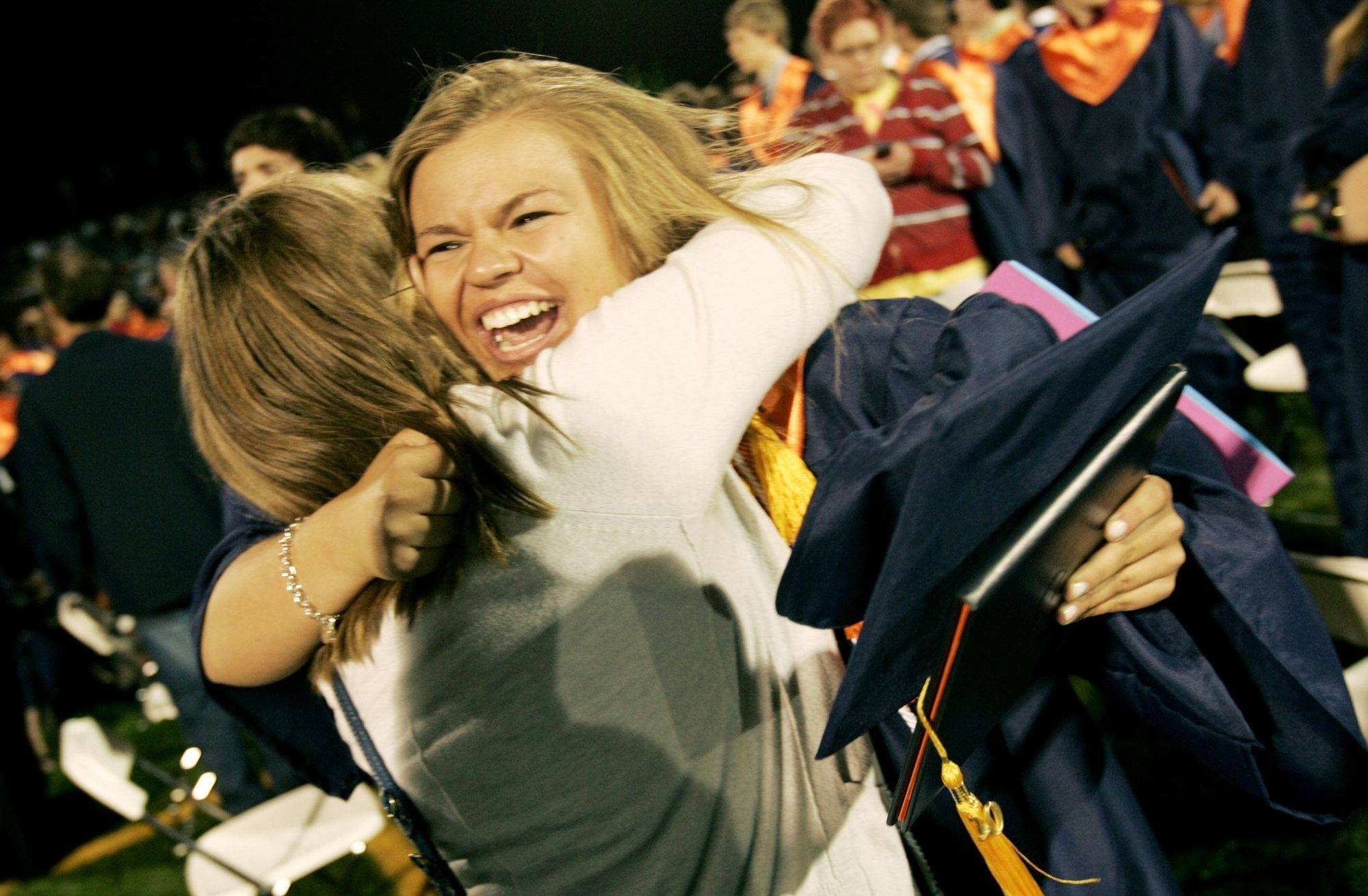 Kelly Devitt, right, gets a hug from her friend, Liz Liddle, left, after her Naperville North graduation Wednesday in Naperville.