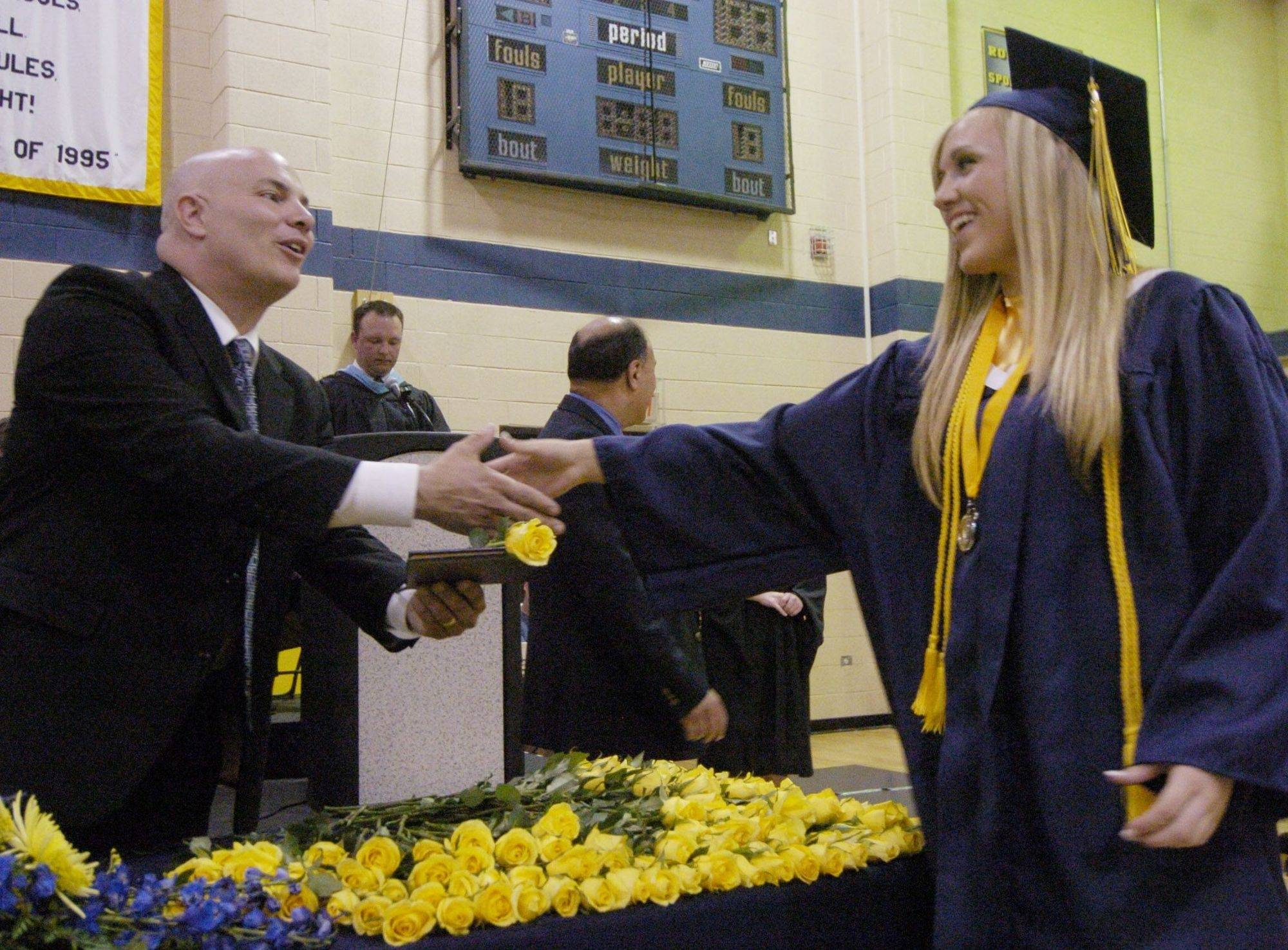 Kristen Lambert receives her diploma and a flower from board of education member Michael Eckhardt during Round Lake High School's graduation Saturday.