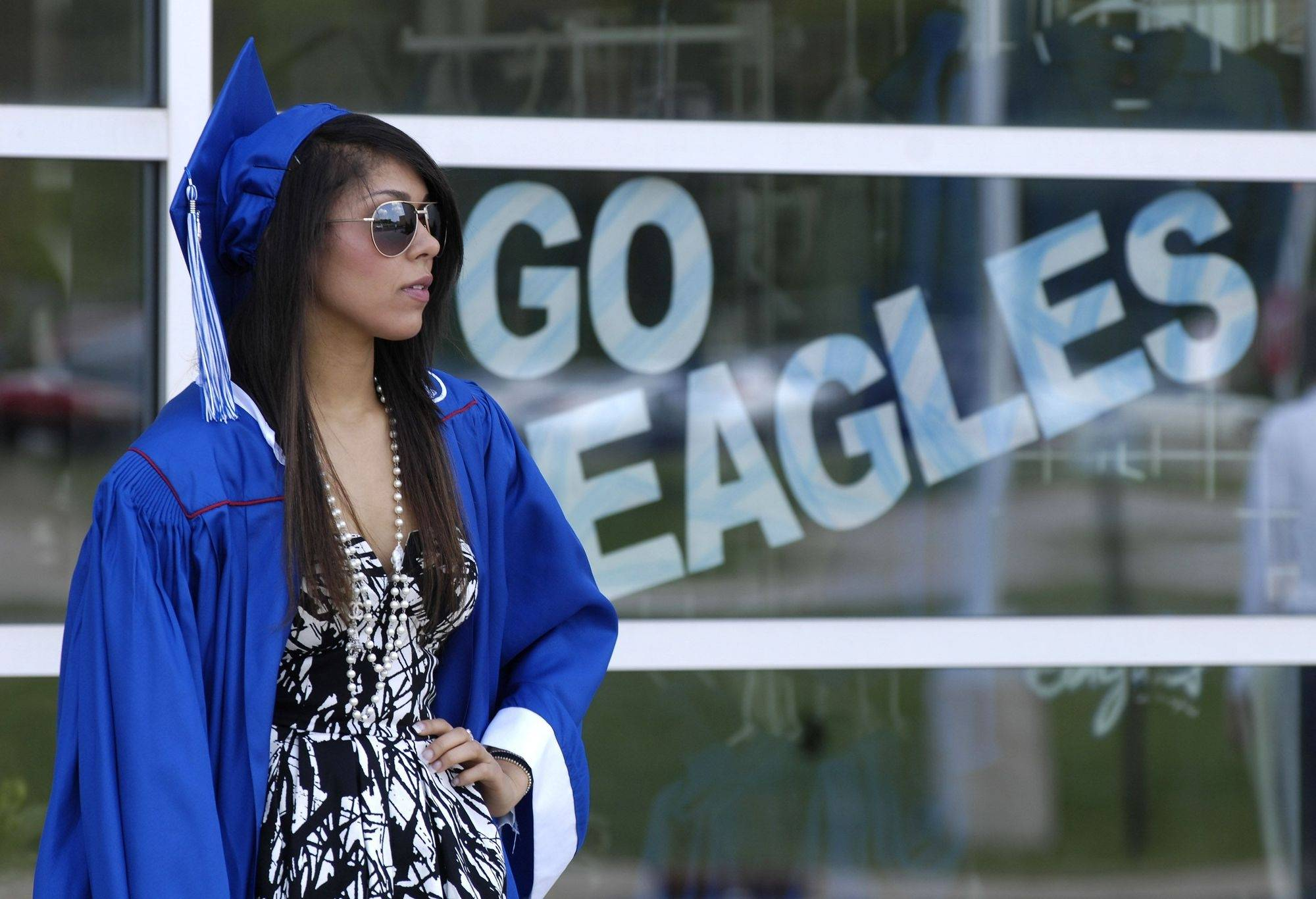 "A ""Go Eagles"" sign near the front entrance is in the background as Josie Roman of Lindenhurst waits outside before the Lakes Community High School graduation ceremony Sunday, May 23, 2010."