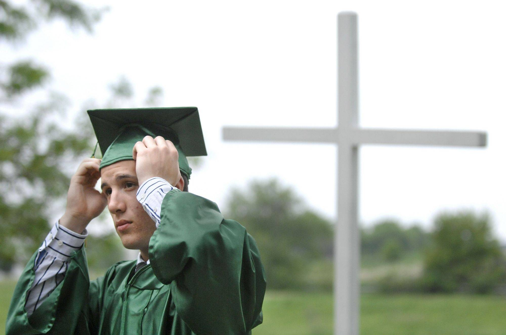 Dylan Kohl adjusts his cap before lining up for the St. Edward commencement ceremony at St. Patrick Church in St. Charles on Tuesday.