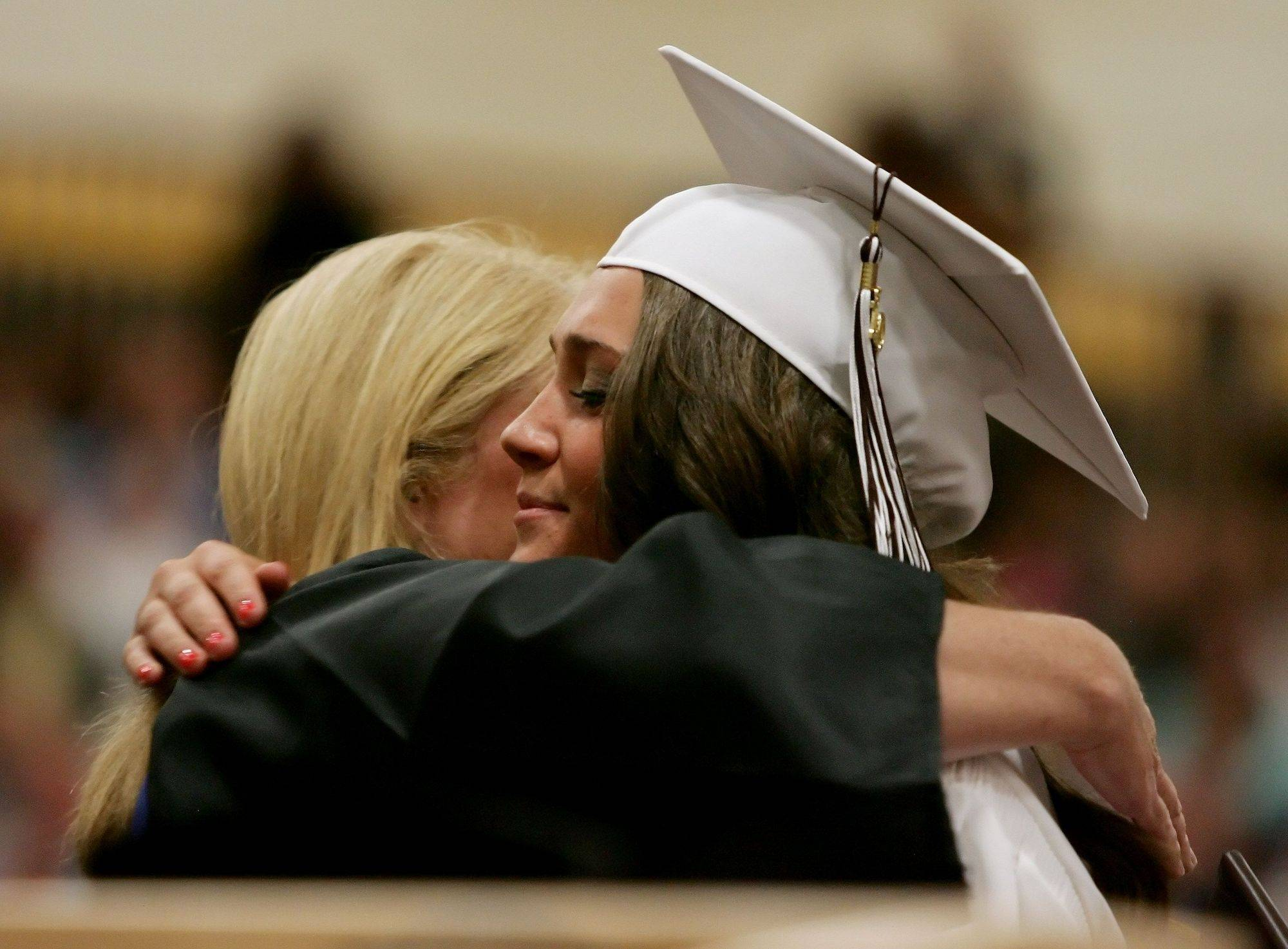 Kelly Brennan hugs her mother and faculty member, Catherine, as she receives her diploma during the graduation ceremony Thursday at Carmel Catholic High School in Mundelein.