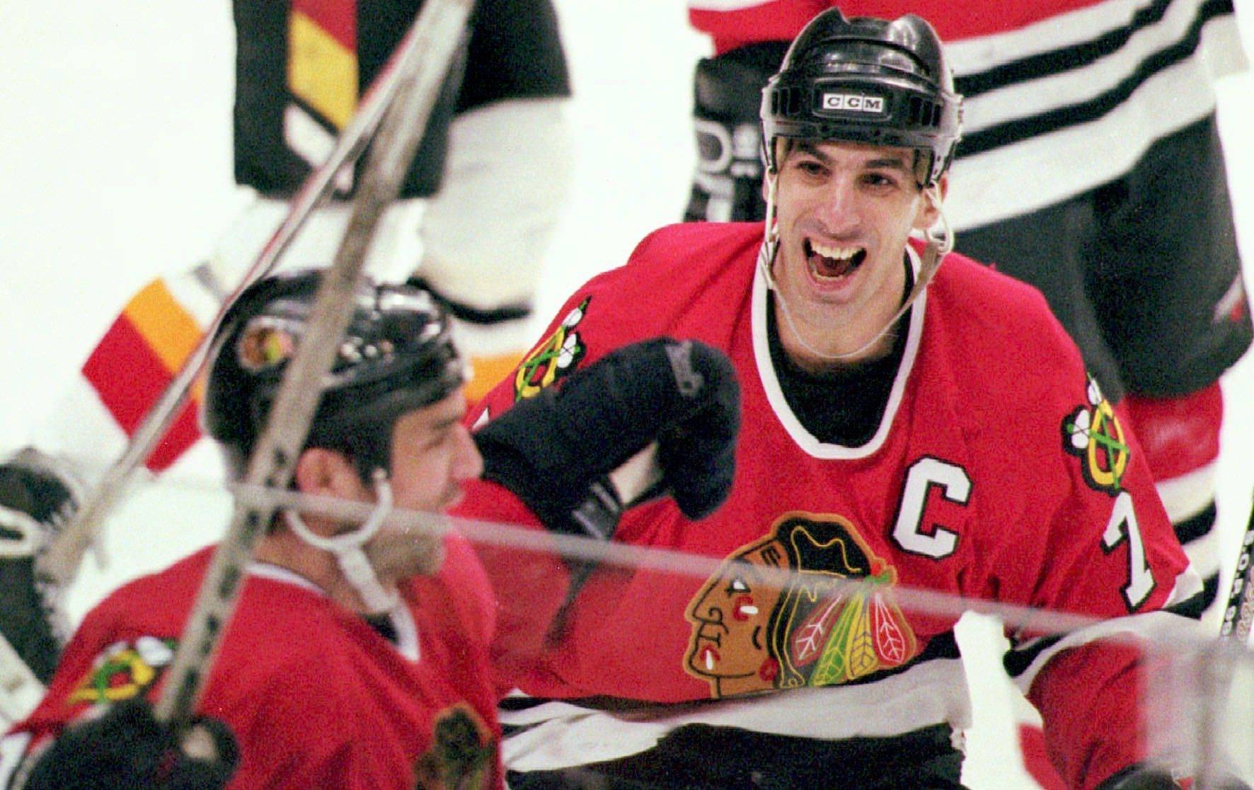 Chicago Blackhawks captain Chris Chelios congratulates teammate Joe Murphy after Murphy scored the game and series-winning goal for the Blackhawks against the Calgary Flames in this April 24, 1996 file photo.