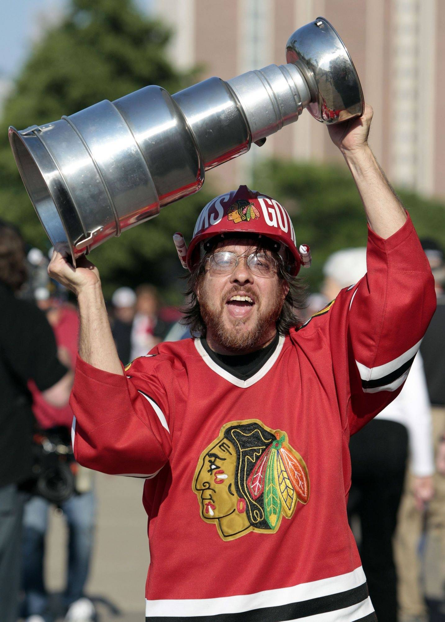 A Chicago Blackhawks fan carries his own version of the Stanley Cup as he arrives at the United Center for Game 1 of the Stanley Cup hockey finals between the Blackhawks and the Philadelphia Flyers.