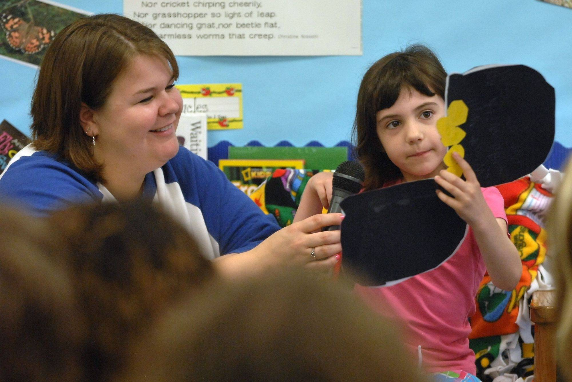 Woodview School first grade teacher Tricia Schmidt helps Kate Royston read her short story a story Friday morning.