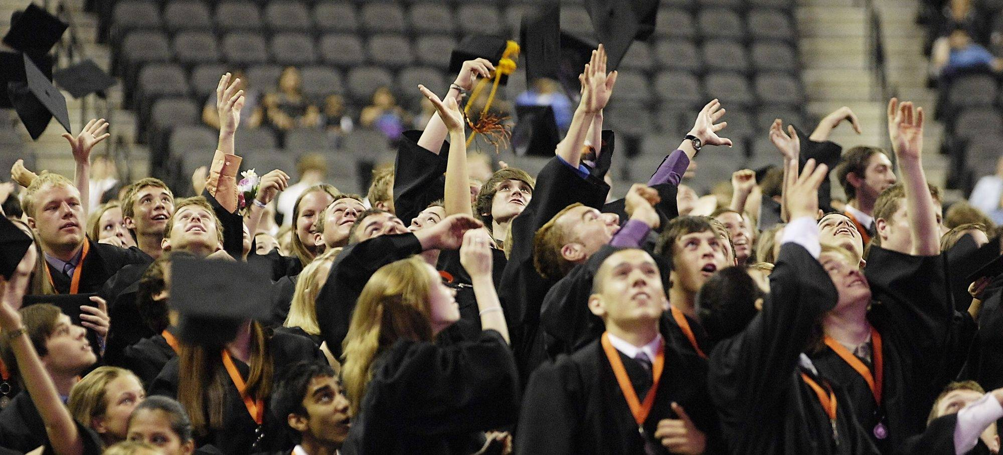 All eyes turn toward the lights as St. Charles East High School 2010 graduates toss their caps at the end of their graduation ceremony Sunday.