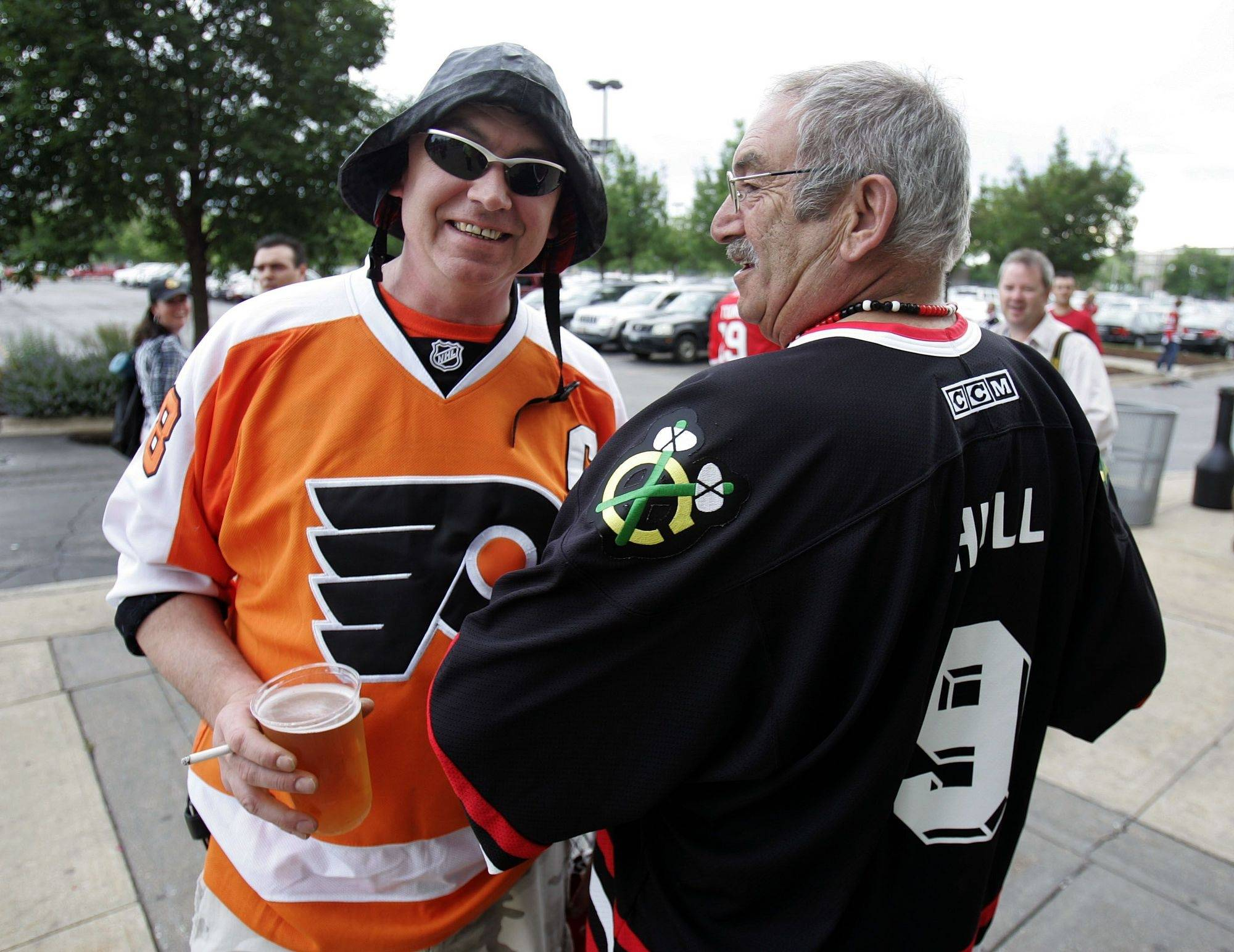 Todd Grouchy, left, and Wayne Bursey, both of Newfoundland, Canada hang out outside the stadium in their opposing uniforms prior to game 5 of the Stanley Cup Finals at the United Center in Chicago Sunday.