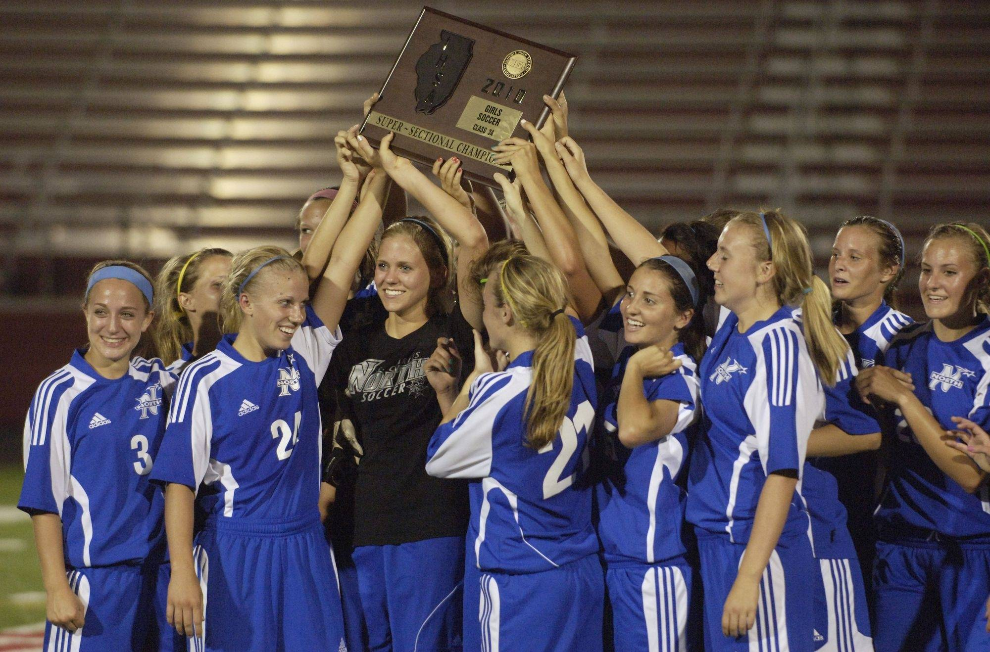 St. Charles North players lift their trophy after defeating Barrington in the Barrington Class 3A girls soccer supersectional.