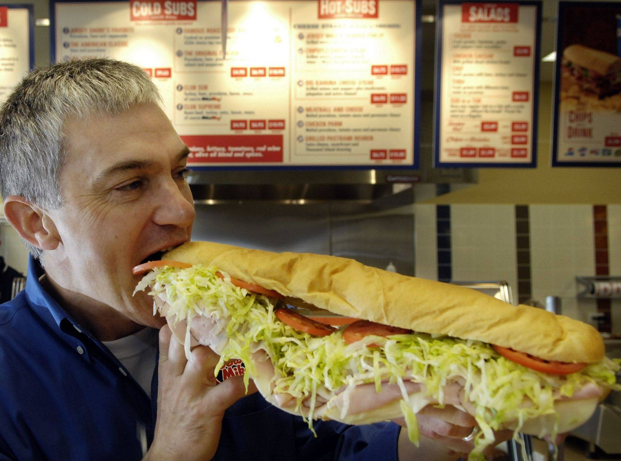"The ""giant"" size sub at Jersey Mike's is truly a mouthful as demonstrated by Jim Shipman, who recently opened a location of Jersey Mike's Subs in Geneva."