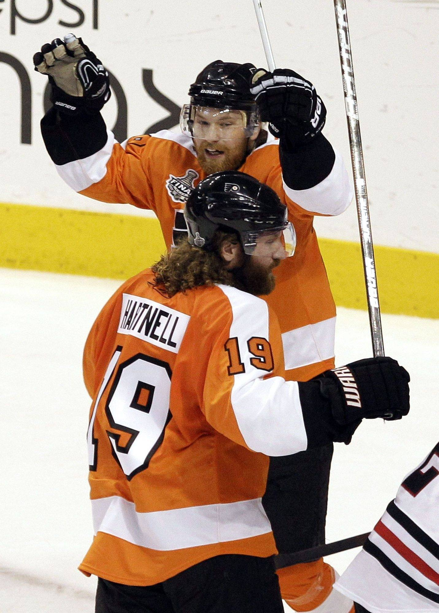 Philadelphia Flyers right wing Claude Giroux, top, celebrates with left wing Scott Hartnell after Hartnell scored against the Chicago Blackhawks in the first period.
