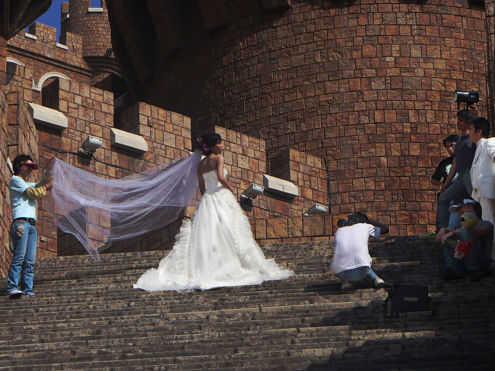 During a school trip to China, a bride was having pictures taken at a castle in Dalian, China.