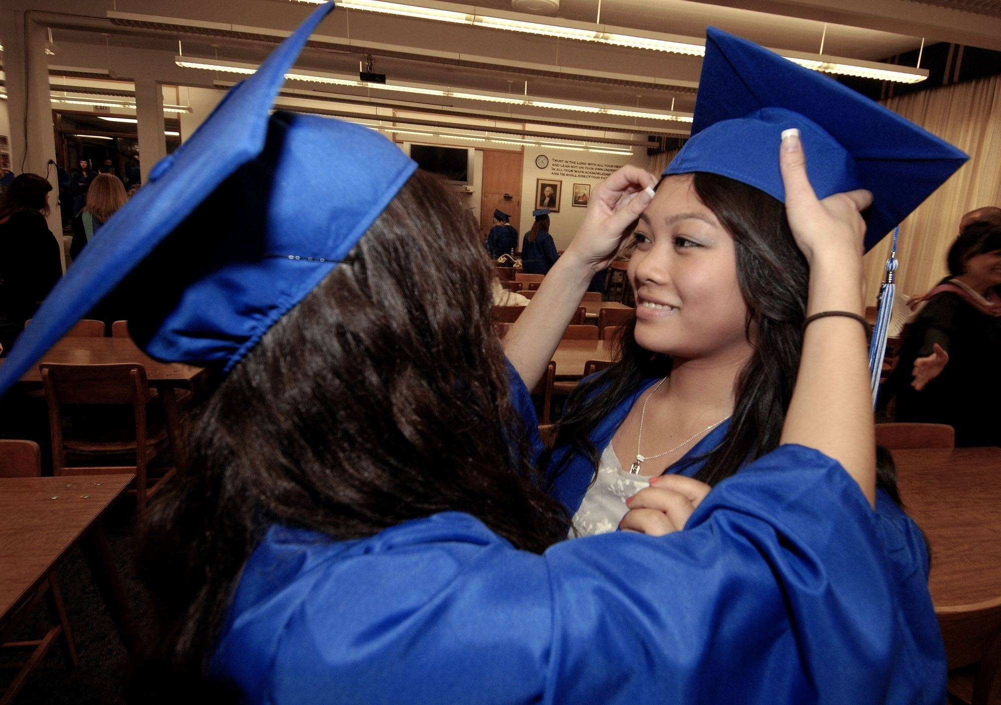 Annah Walton of Chicago help Leyanne Gonzalez of Hanover Park with her mortar board before the Christian Liberty Academy holds its 8th grade and high school graduation ceremonies on Sunday, June 13 in Arlington Heights.
