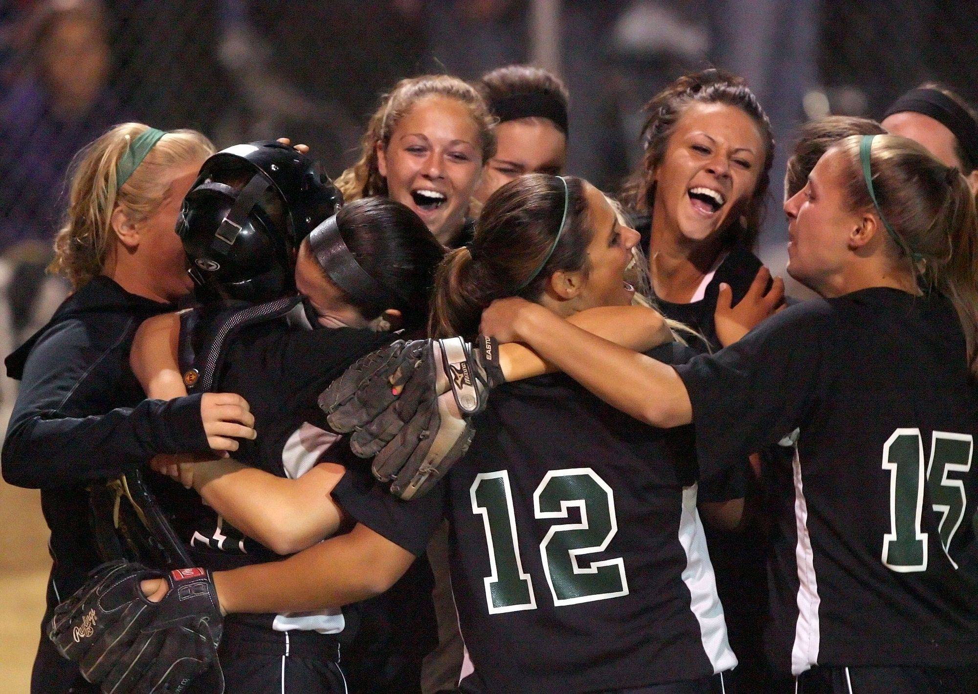 Fremd players celebrate after beating New Trier 4-0 to win the super-sectional softball title Monday at Rolling Meadows High School.