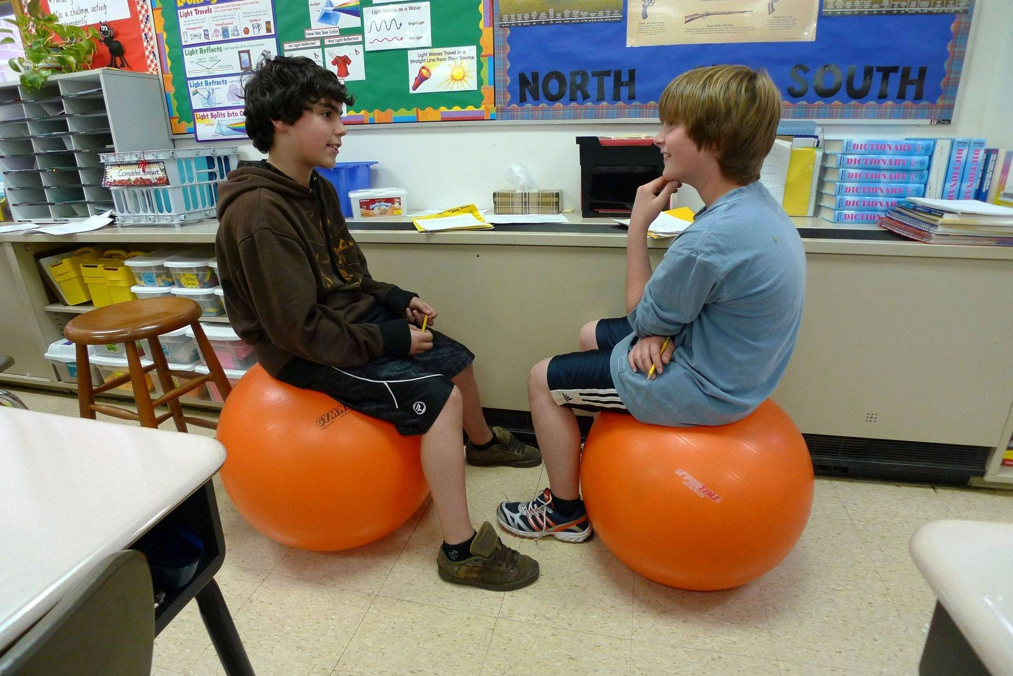 Danny Peters, left, and Max Tuhey, right, chat about a writing project they're working on. Fifth graders at Park View School in Lombard are experimenting with sitting on stability balls instead of regular chairs.