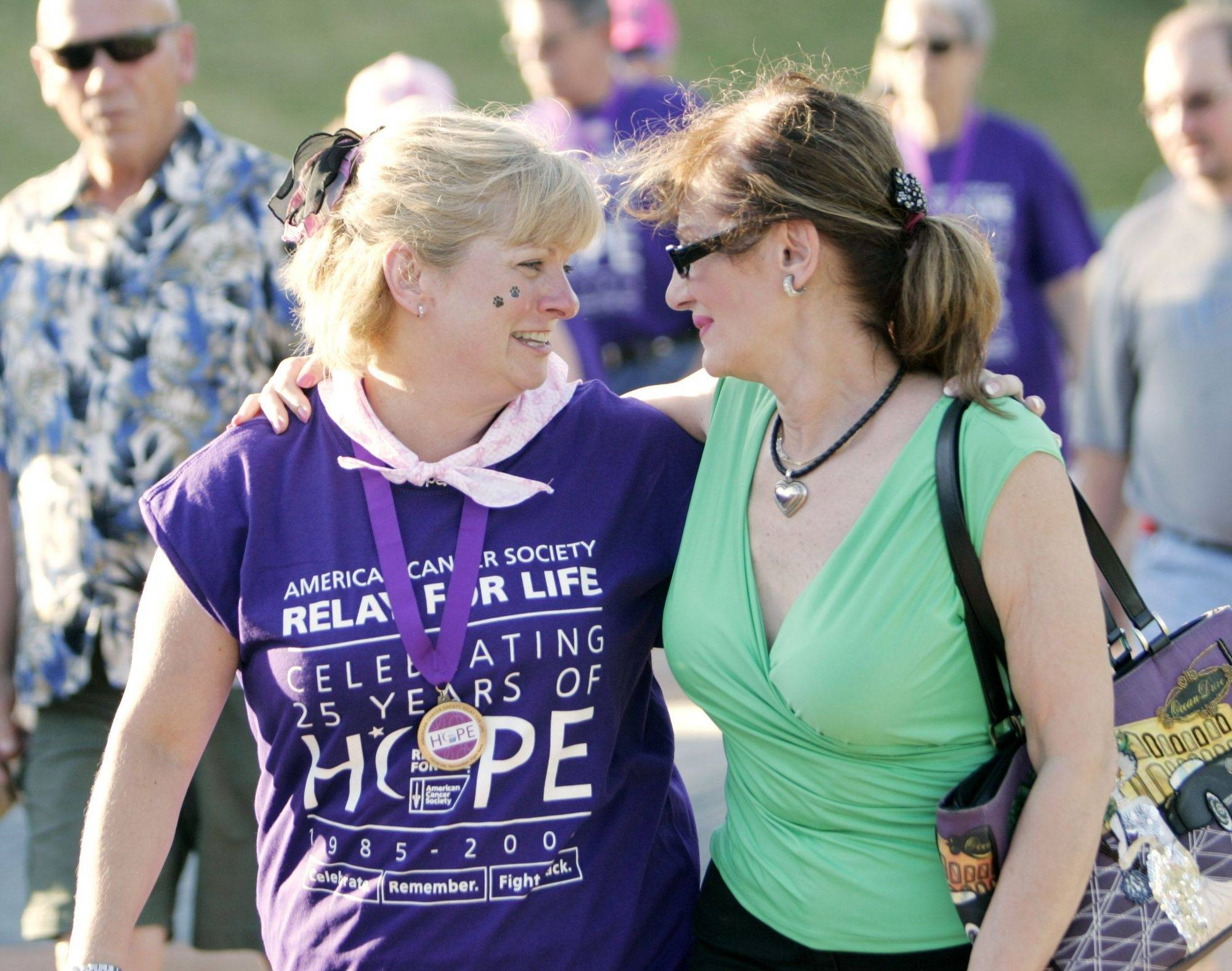 Denise Woodard, left, and Irene Burgen of St. Charles come together during the survivor's lap of last year's Relay For Life of Kane County at Elfstrom Stadium in Geneva.