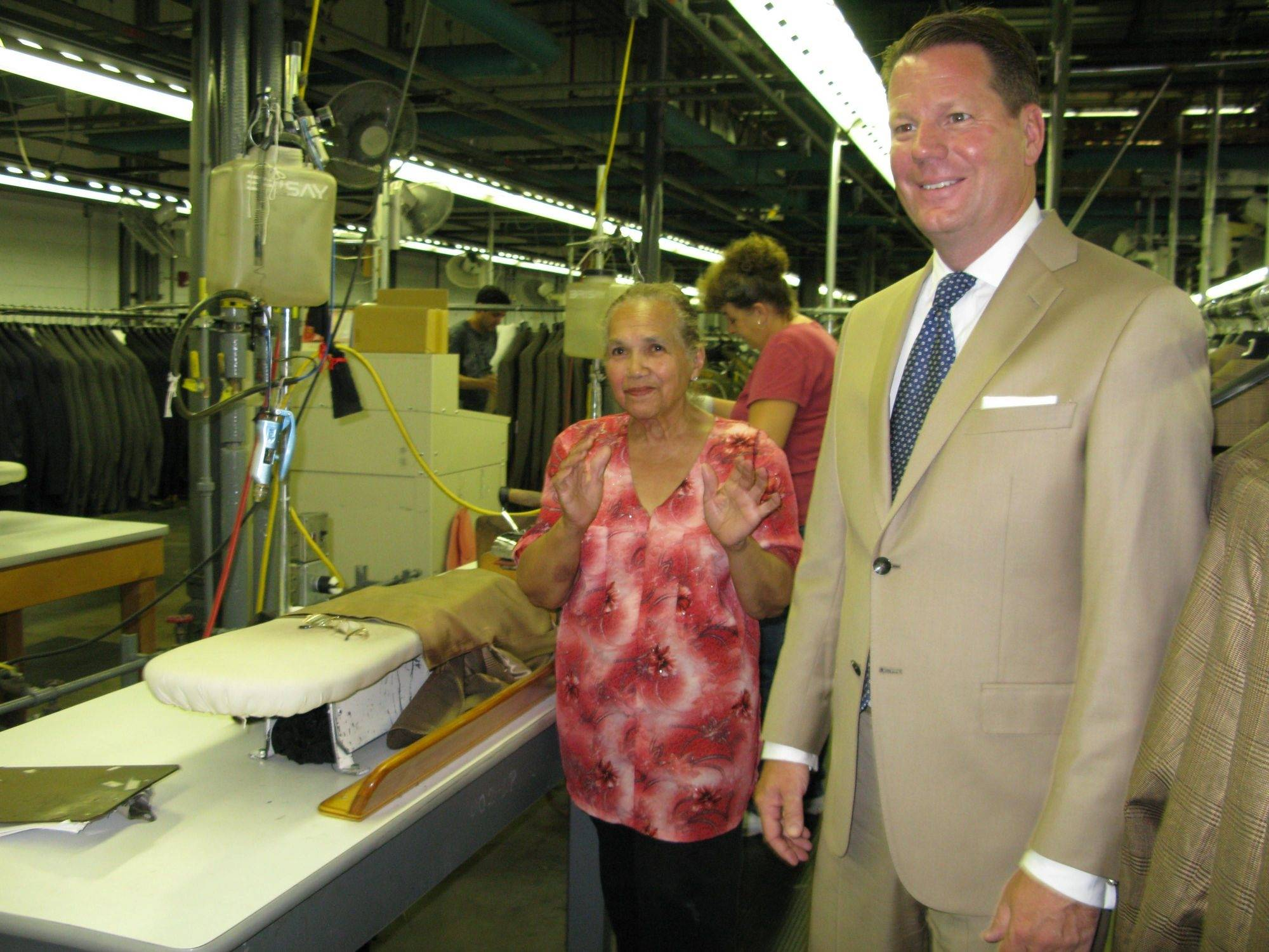 Doug Williams, CEO of HMX LLC, formerly Hart Schaffner Marx, visits with 65-year-old Marina Franceschi, one of the longest-serving employees of the Des Plaines suitmaker. Franceschi said she was reassured after Williams' visit that the factory won't be closing in the near future.