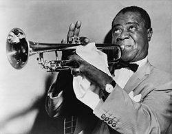 One of the first jazz singers most likely was the world famous trumpeter and gravely voiced singer Louis Armstrong.