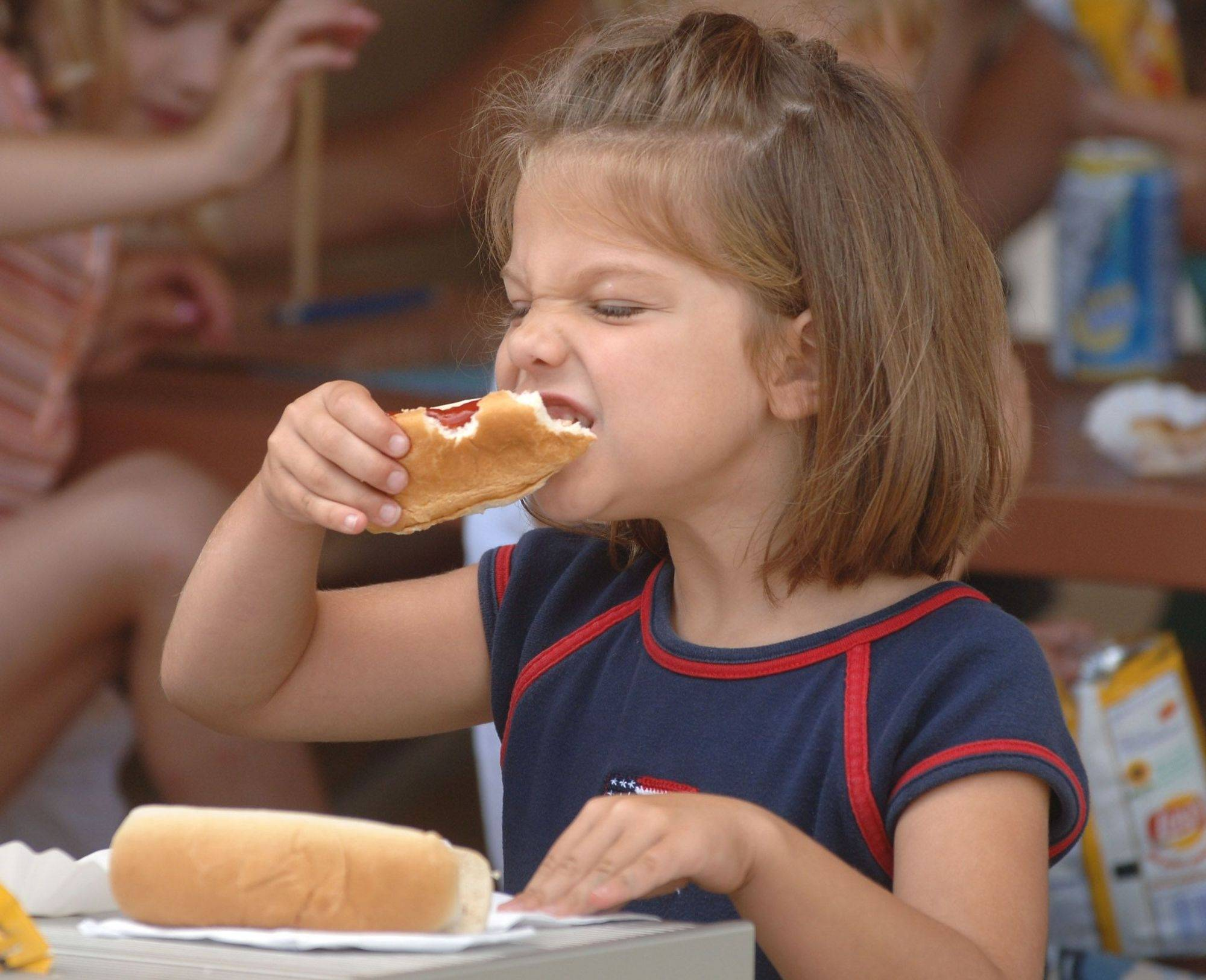 Hannah Miller of Island Lake digs into a free hot dog at the Island Lake family picnic in Veterans Park on the Fourth of July.
