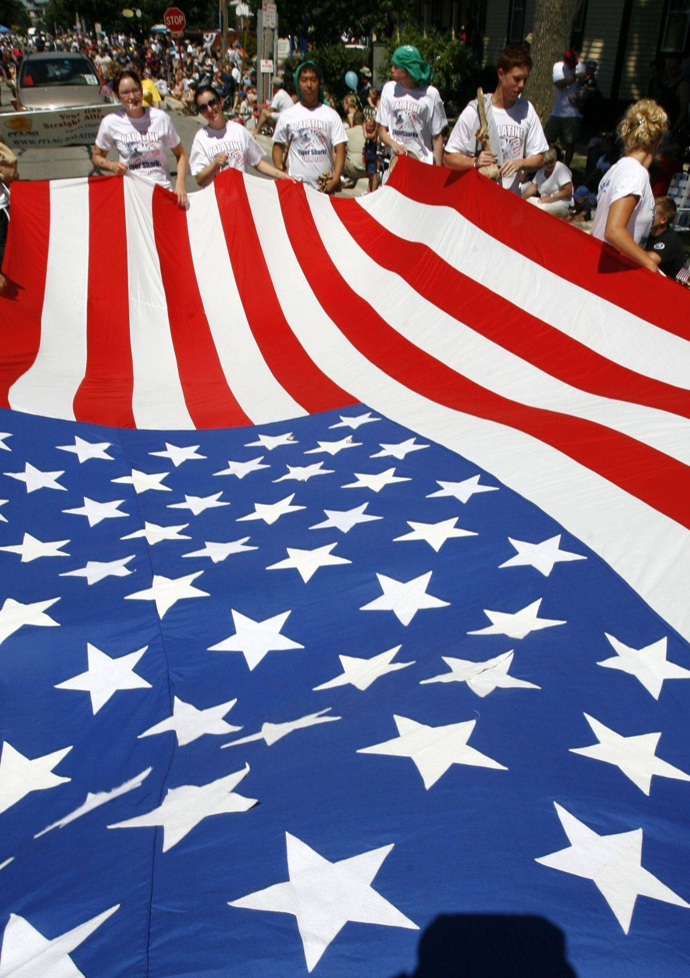 Palatine's Tiger Shark swim team carry a large American flag in Palatine's Fourth of July parade on Saturday July 3.