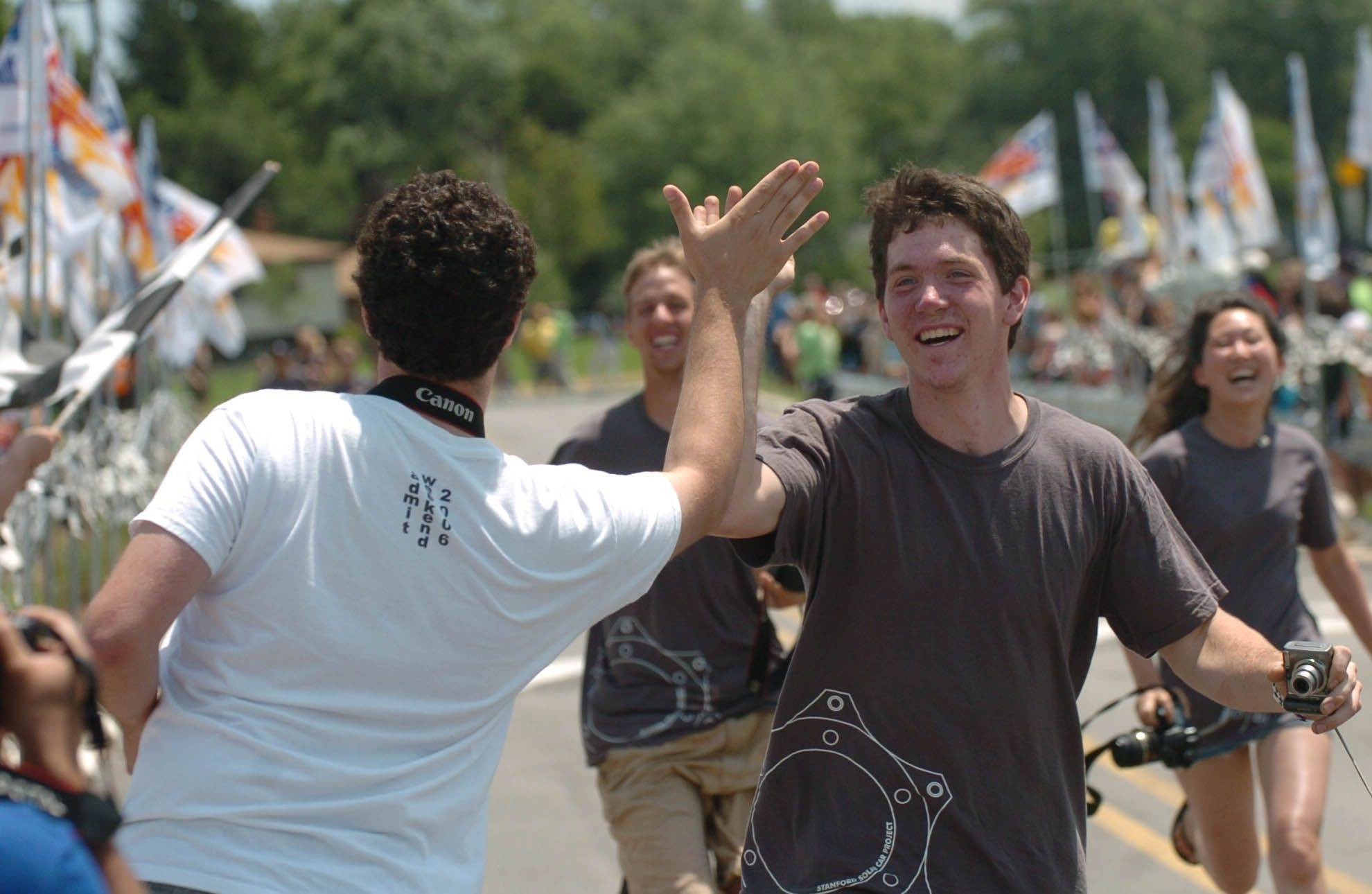 Sasha Zbrozek, left of Stanford University gives a high five to fellow student Paul Karplus after their car won a race which was part of the American Solar Challenge and Naperville Sustainability Challenge.