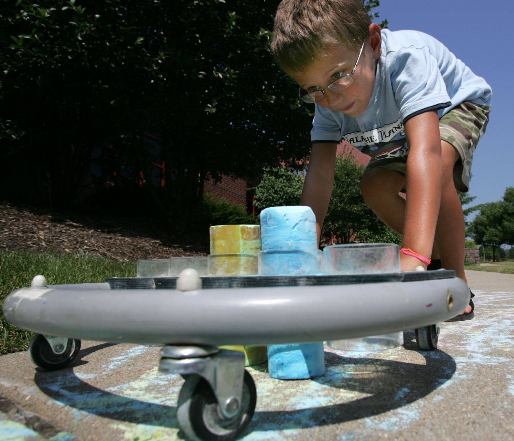 Dmitry Godlevsky, 7, tries out a sidewalk chalk drawing device designed for children who use wheelchairs. Staff from the Northwest Special Recreation Association worked with children this week.