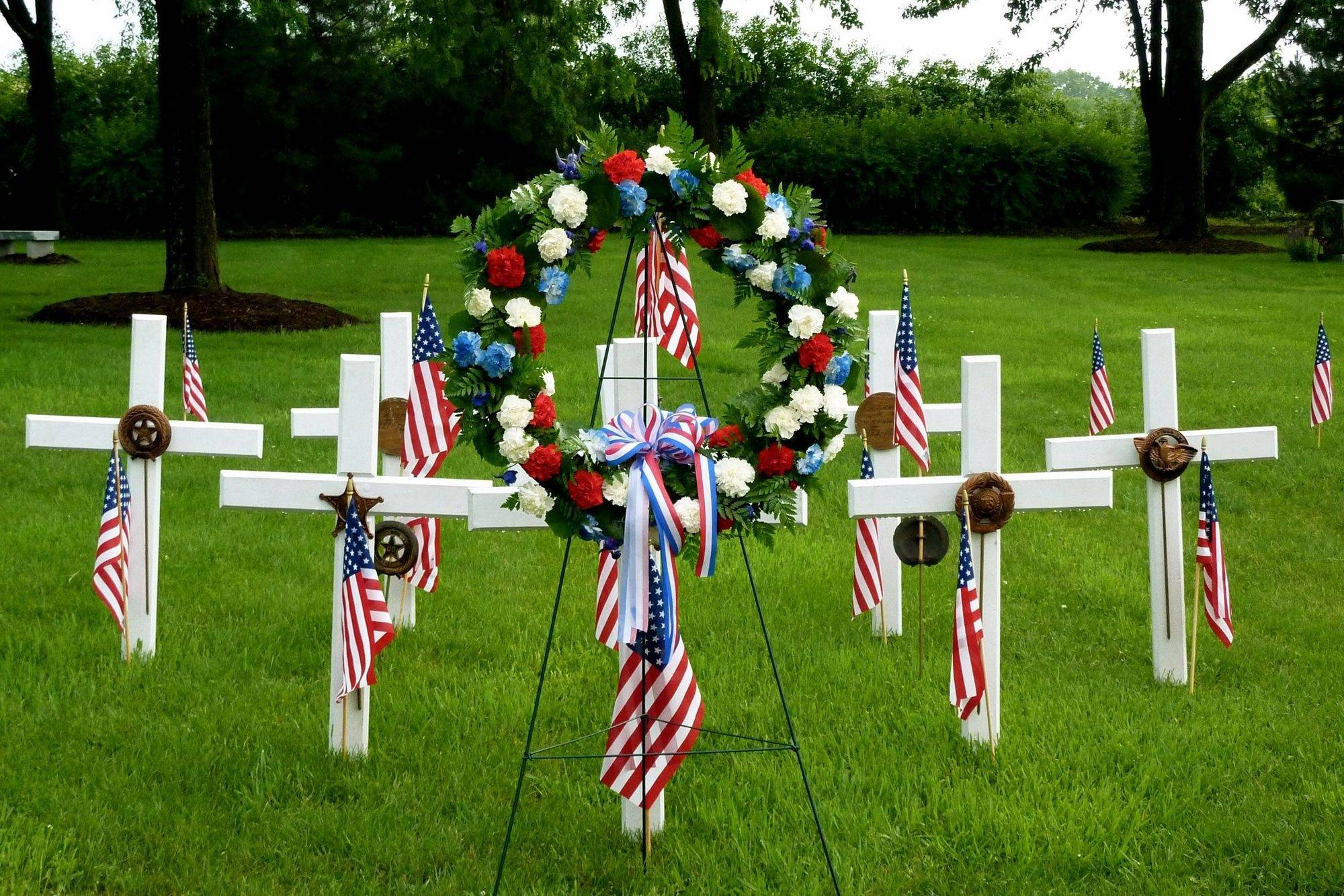Memorial display items were placed at Trinity Lutheran Cemetery in Roselle as part of the Memorial Day service conducted by American Legion Post 1084. The crosses carry medallions representing military service.