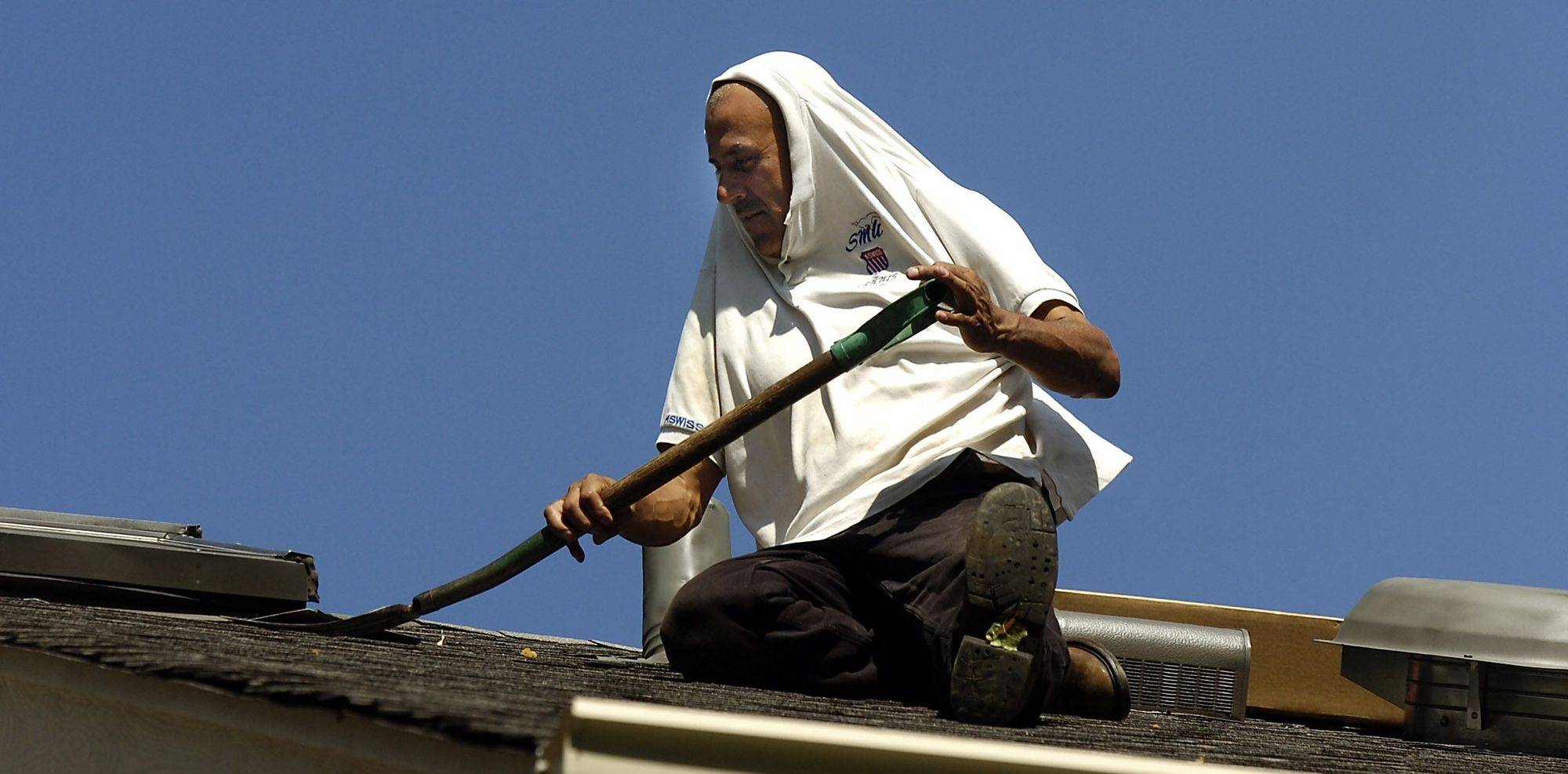 Replacing the skylights on the roof of a home in Bartlett, Salvador Hernandes of St. Charles uses his extra large shirt to shield himself from the sun as he uses a pitchfork to lift up the shingles.