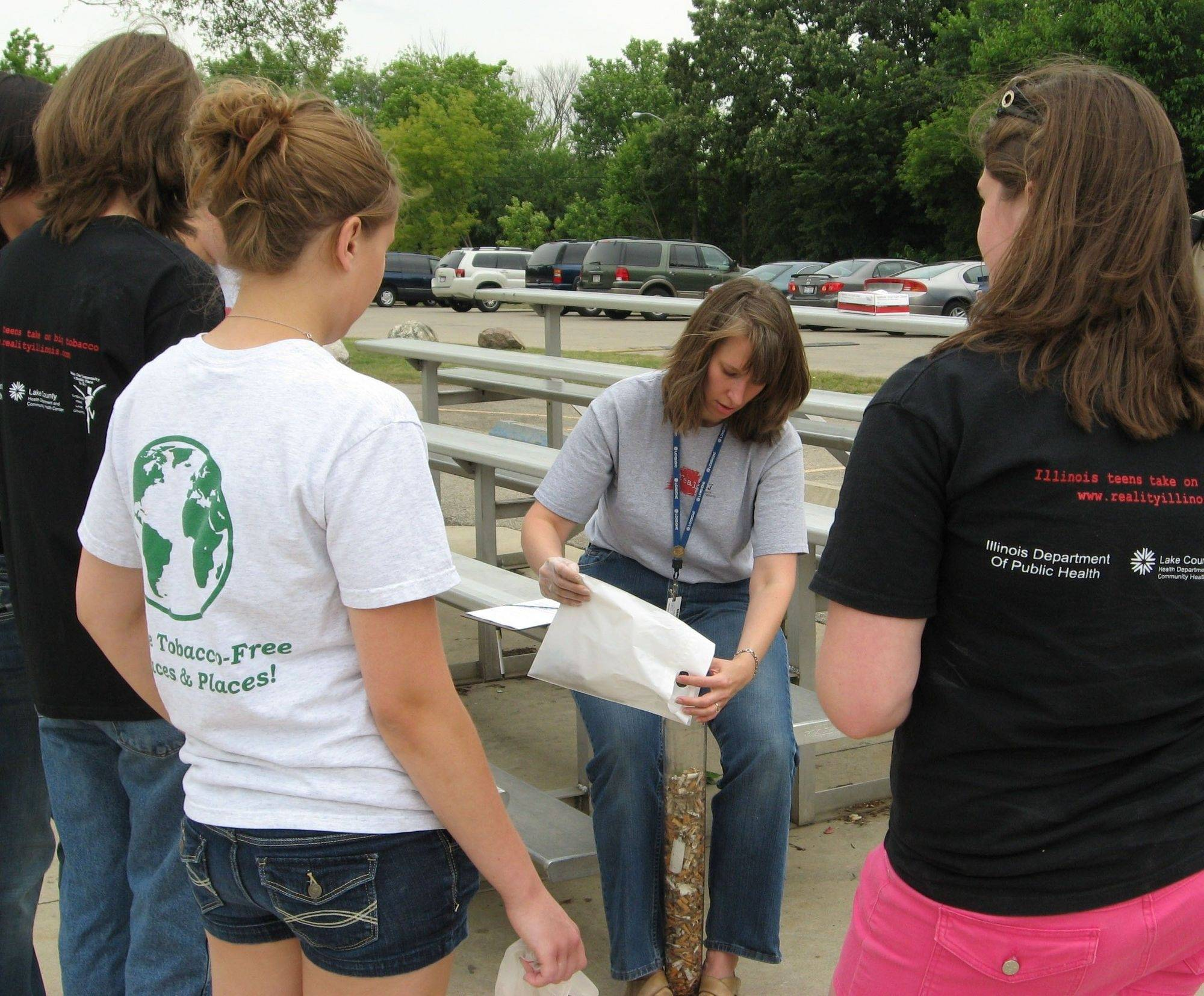 Teen members of REALITY Illinois watch as Barbara de Nekker fills a plastic tube with cigarette butts collected at the skate park in Round Lake Beach.