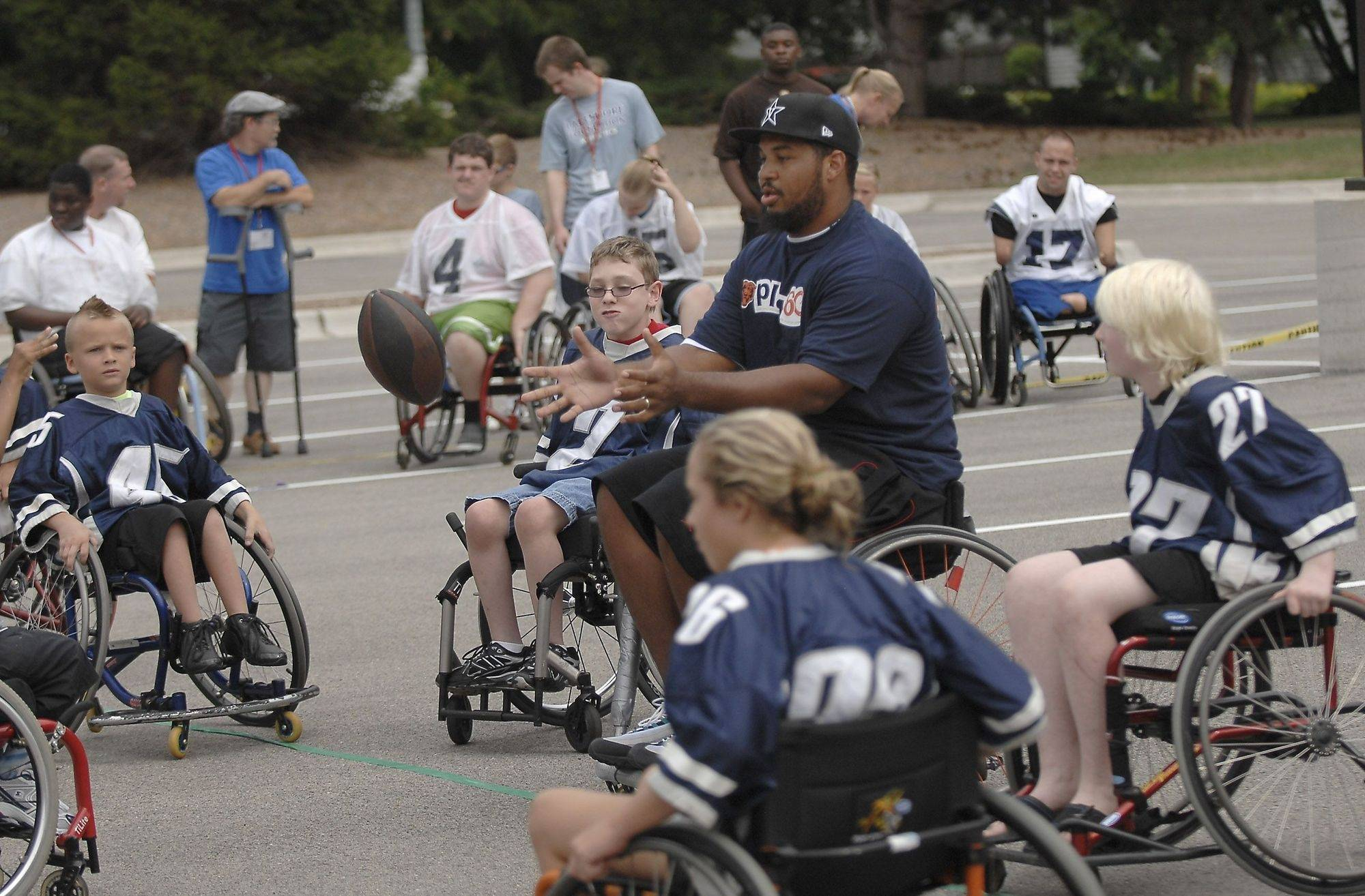 Chicago Bear Chris Williams eceives the snap as he quarterbacks during a wheelchair football game at the National Junior Disability Championship at Lake Forest High School Monday in Lake Forest