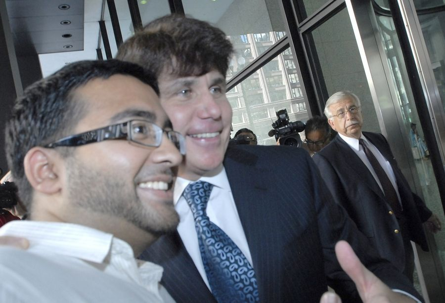 Former Gov. Rod Blagojevich gives a thumbs-up as he poses for a photo with onlooker Mohammed Ahmed of Wood Dale as he arrives for his corruption trial Wednesday.