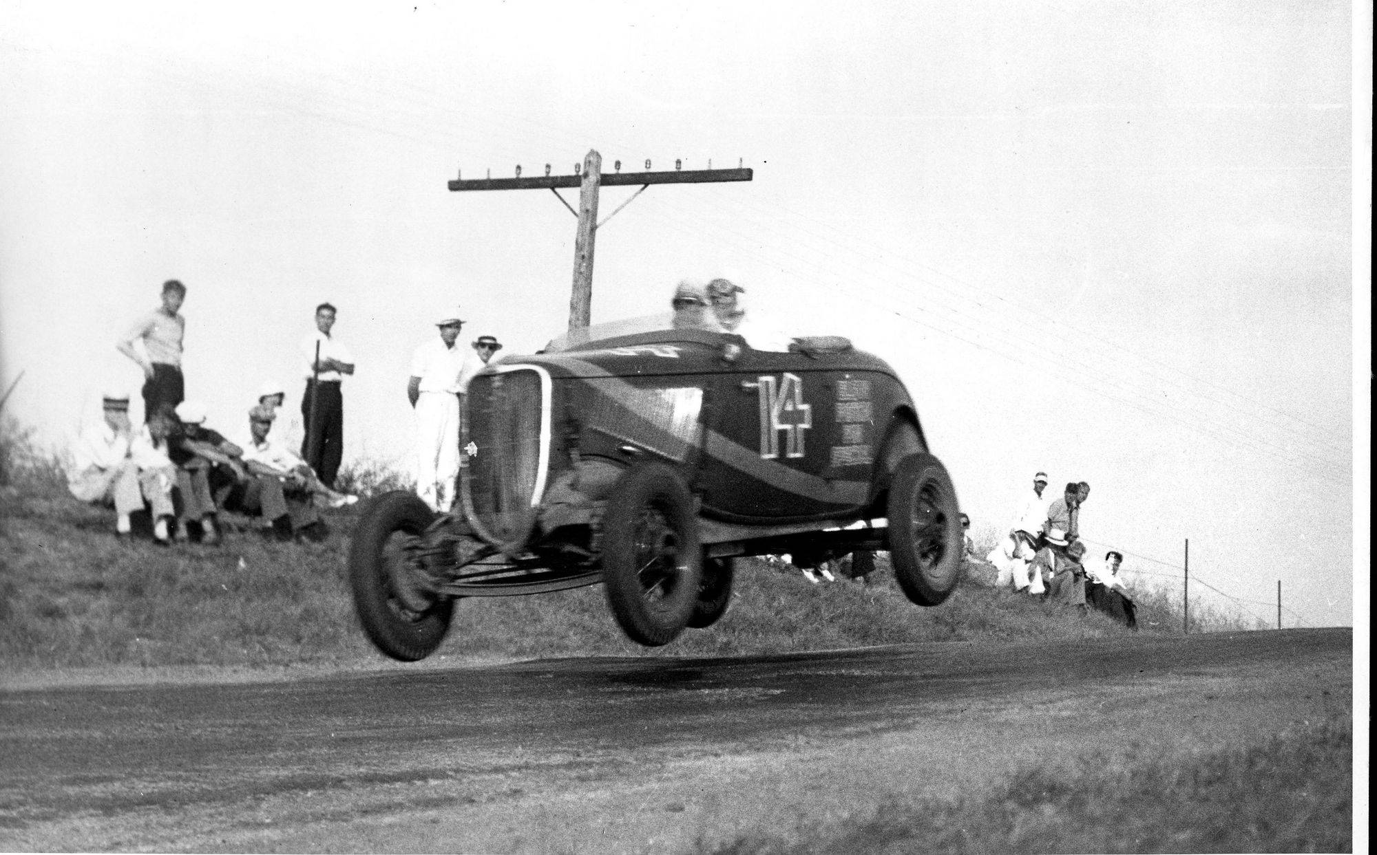 "Frank Briscoe's Elgin Piston and Pin Special car goes airborne at nearly 95 mph on ""The Hump"" on Highland Avenue in the 1933 races."