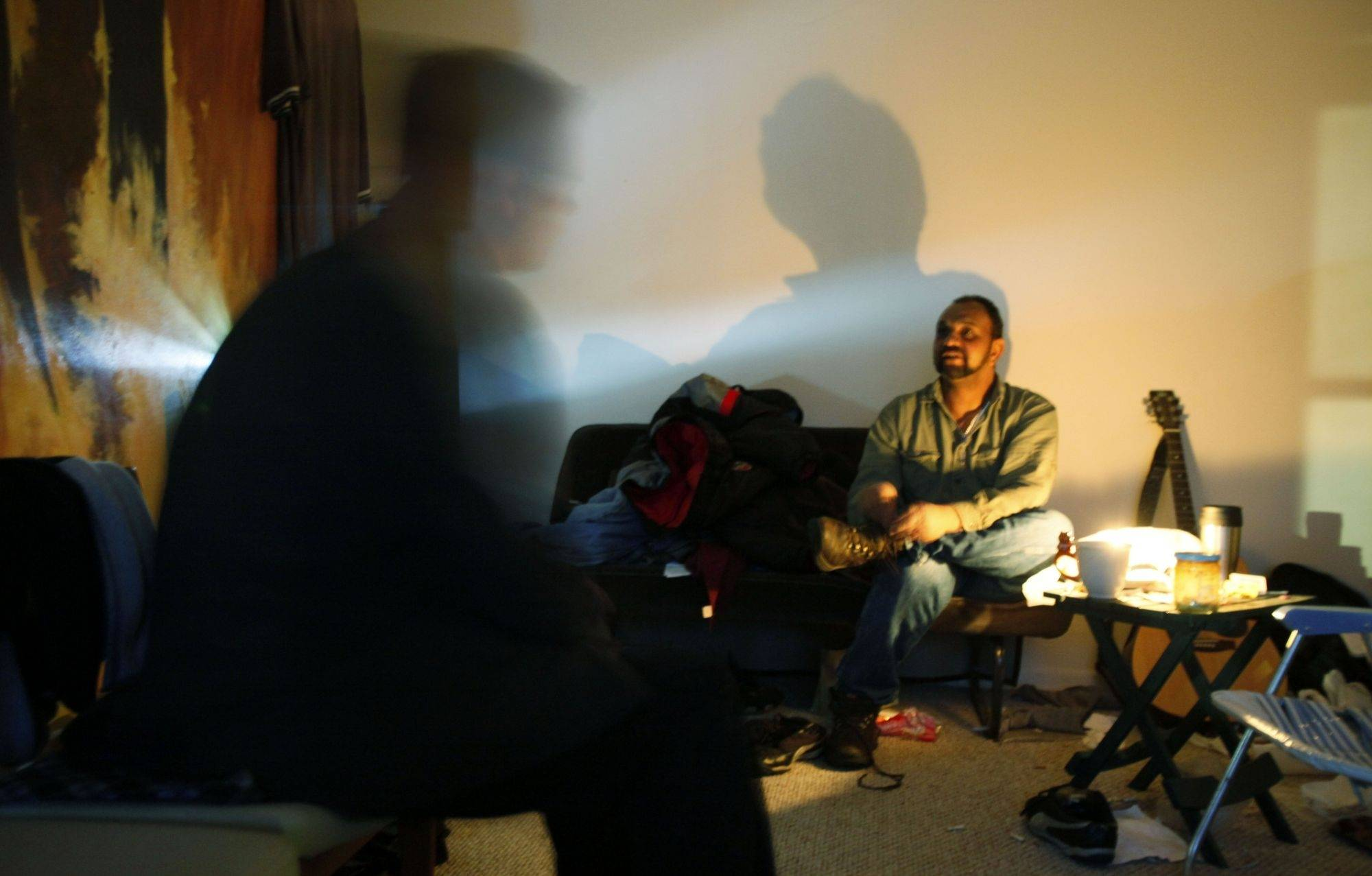 Matt Soerens talks with Sundanese immigrant Mohammed Osman in Osman's apartment that has no electricity in Glen Ellyn
