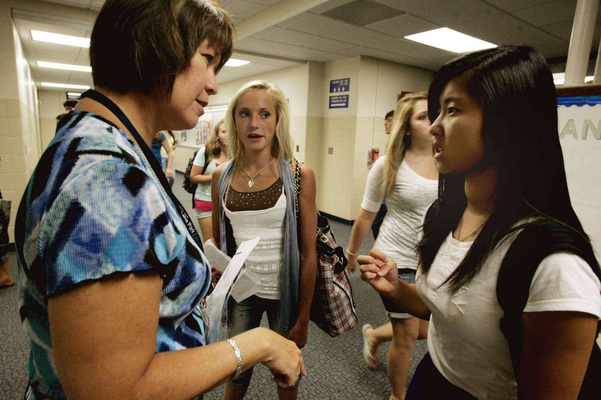 Lake Park High School spokeswoman Jennifer Jungel, left, helps freshmen Rachael Hansen and Michelle Park get to their classrooms Monday during the first day of classes in Roselle.