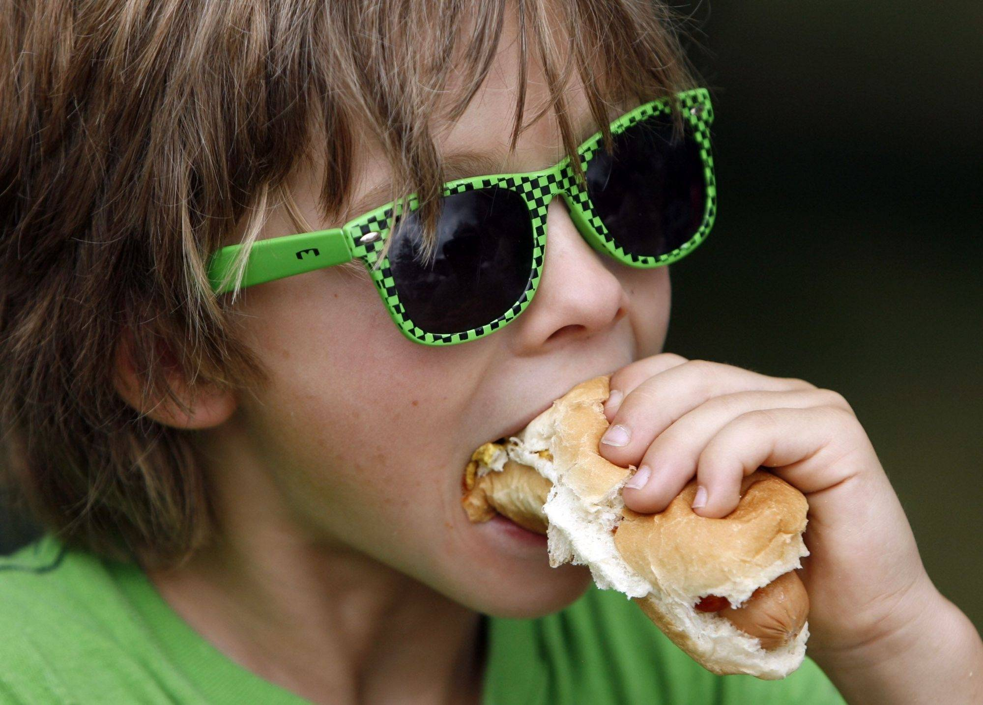 Nathan Gowe, 6, of Gurnee, enjoys a hotdog on a hot day at Gurnee Days in Viking Park Saturday, August 14.